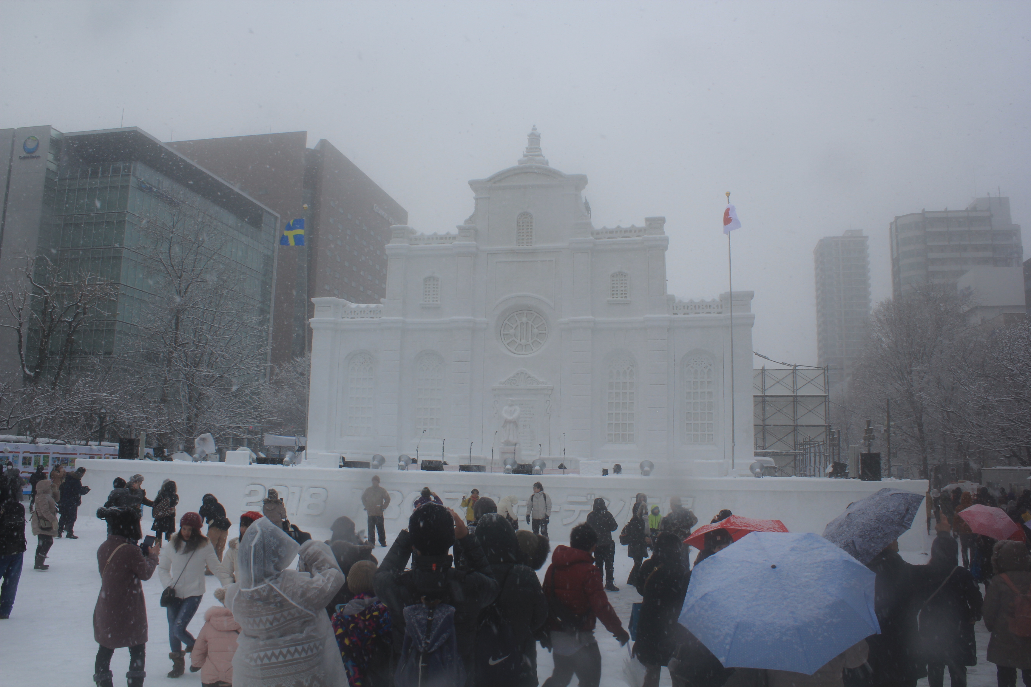 A snow sculpture of a palace at Sapporo Snow Festival with people satnding in front of it