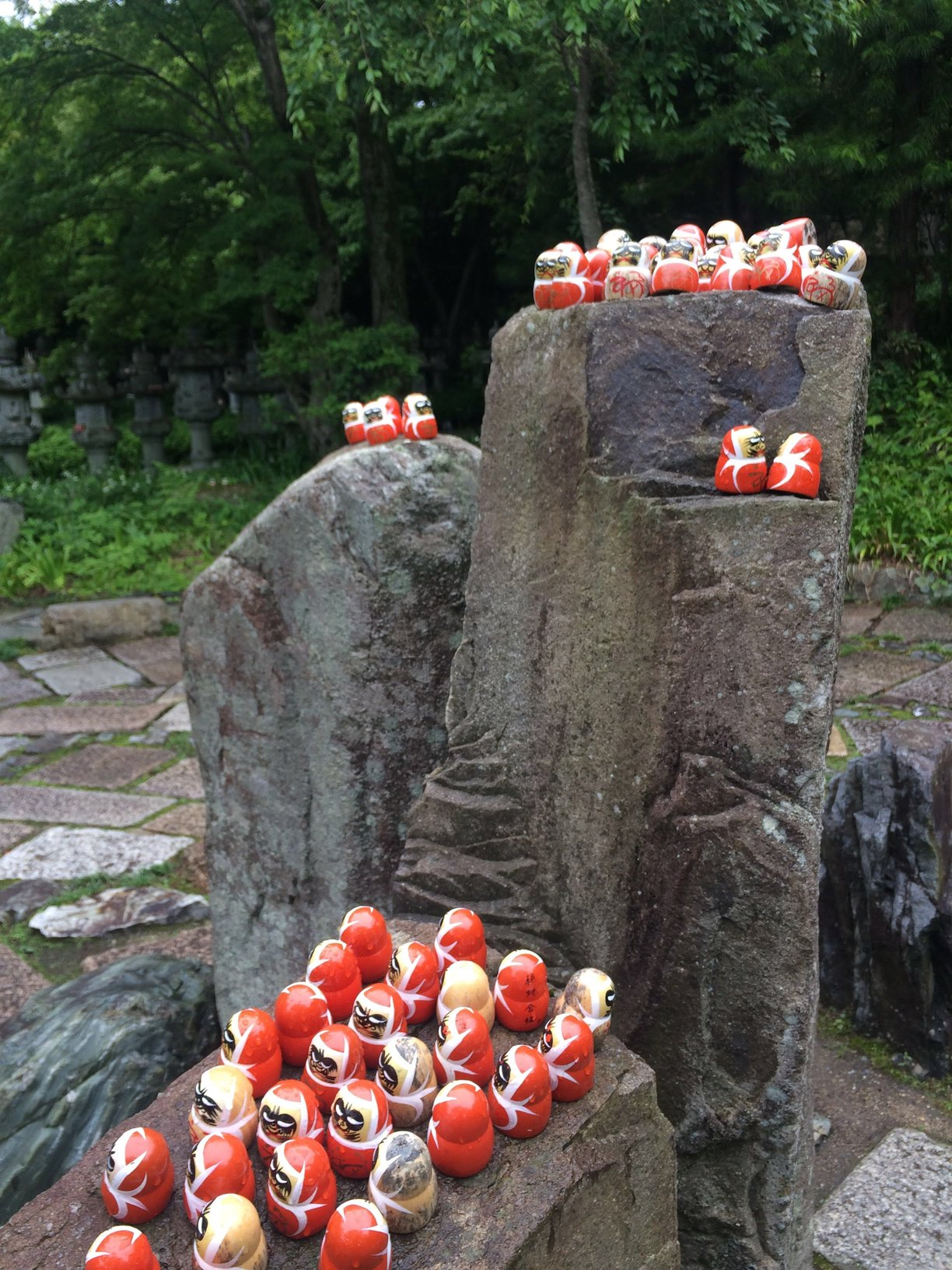 photograph of rocks upon which daruma dolls are kept