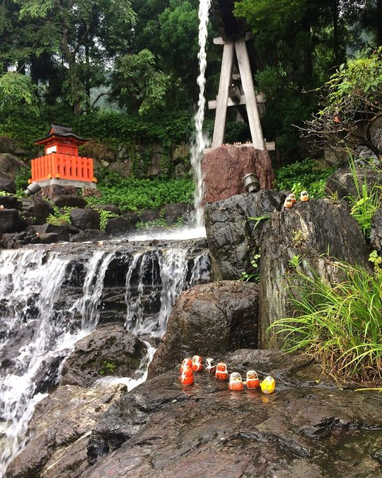 a temple site with a small waterfall and daruma dolls