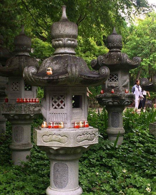 three pillars lined with daruma dolls
