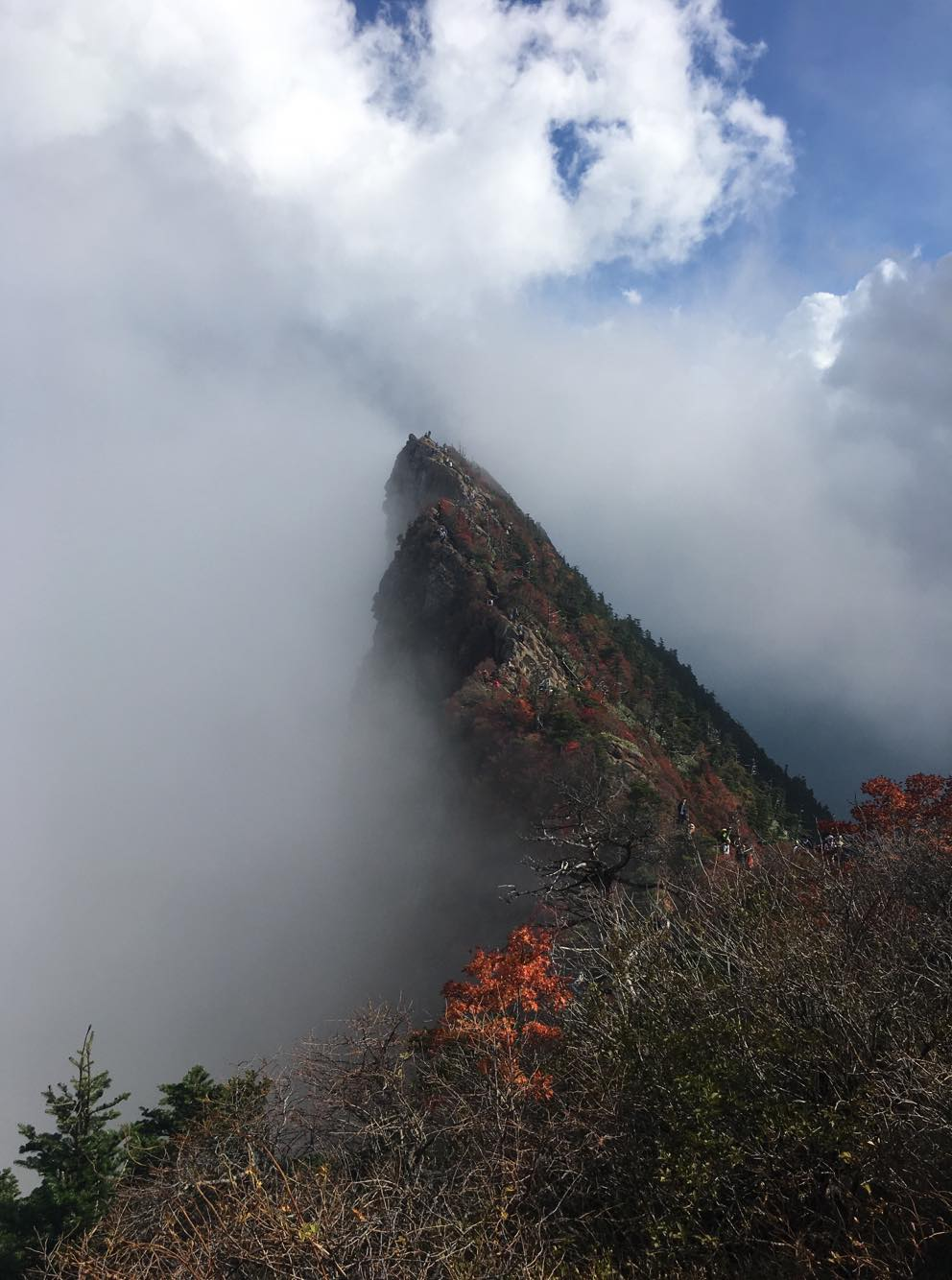 A view of a cliff side beset with clouds