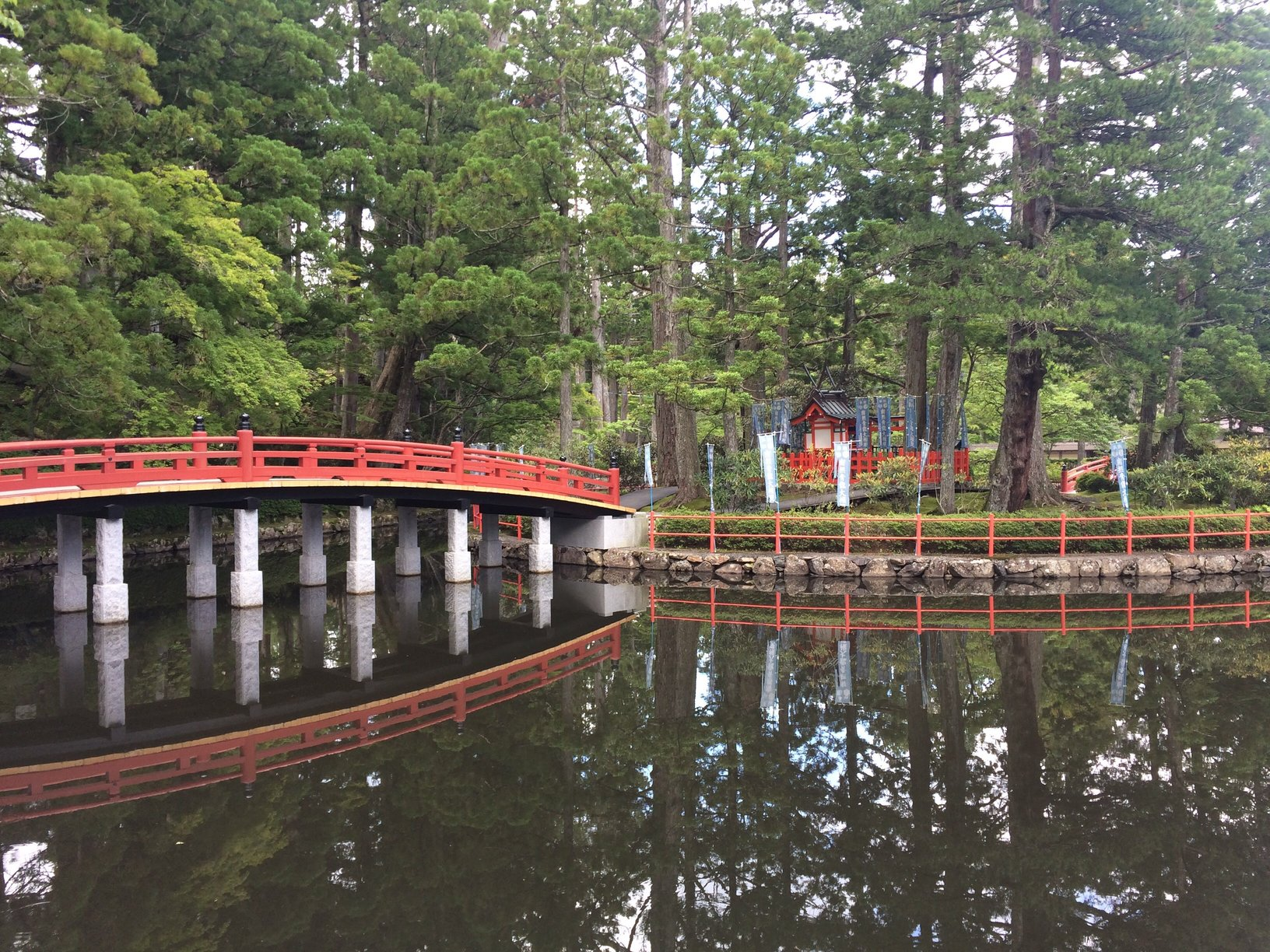 photo of a lake by a wood with a bridge