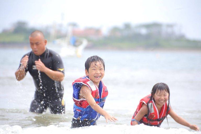 A man and two children playing in the water with great happiness