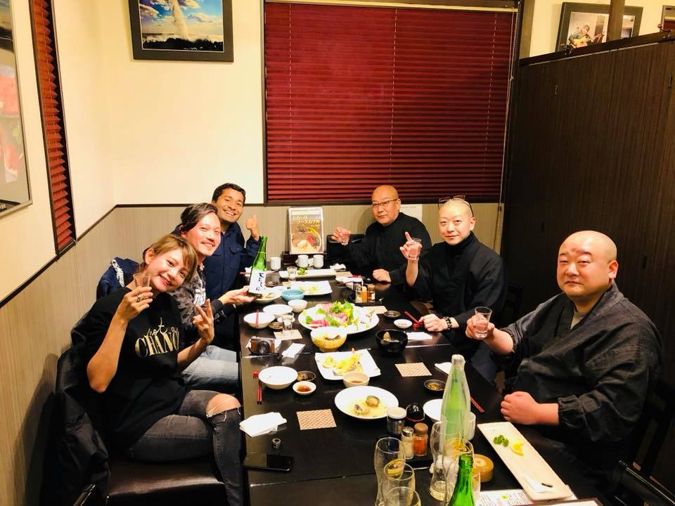 photograph of Nishant and his friends at a restaurant drinking sake and eating sashimi with the monks