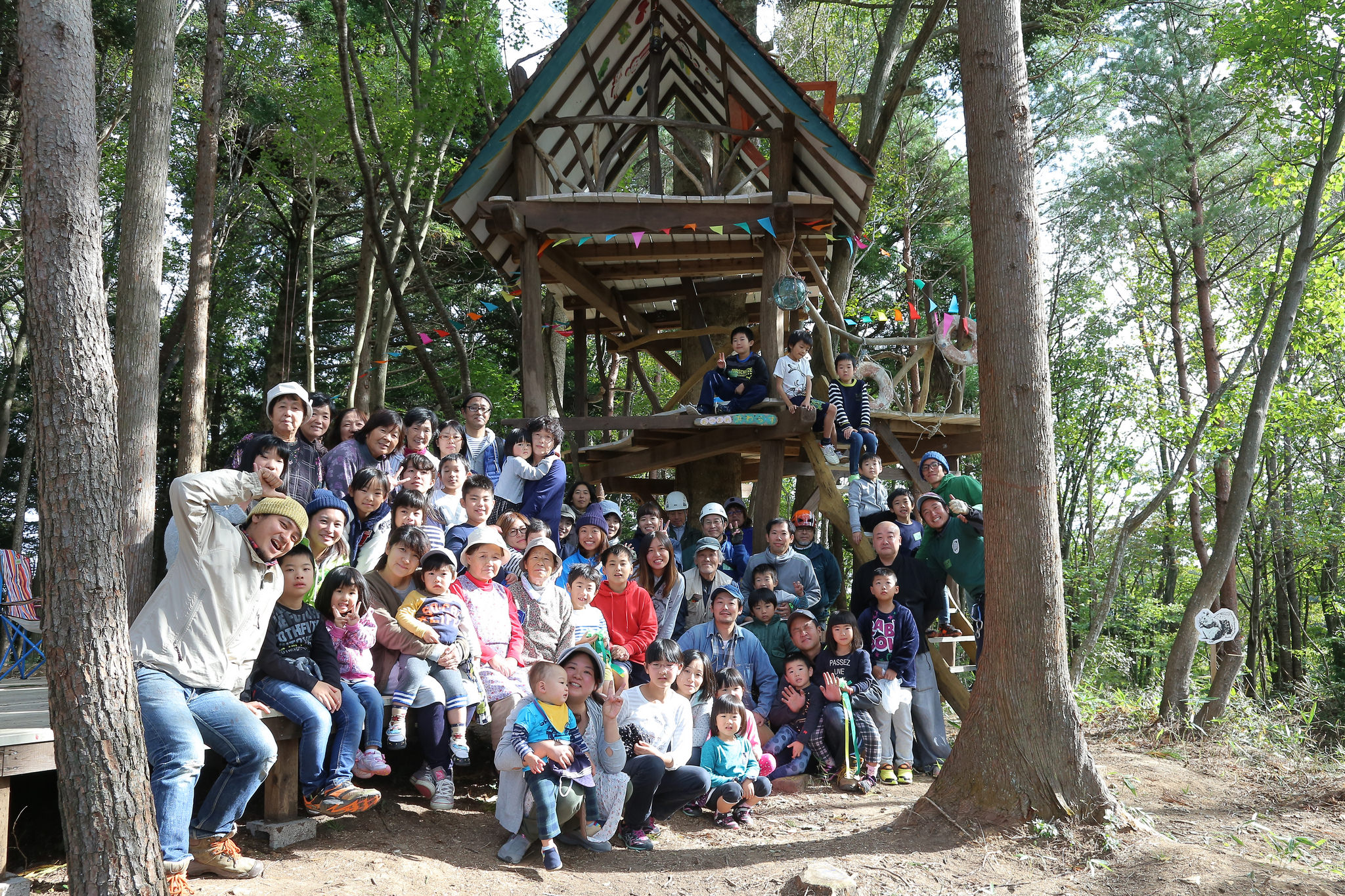photograph of a group of people and children posing in front of a tree-house