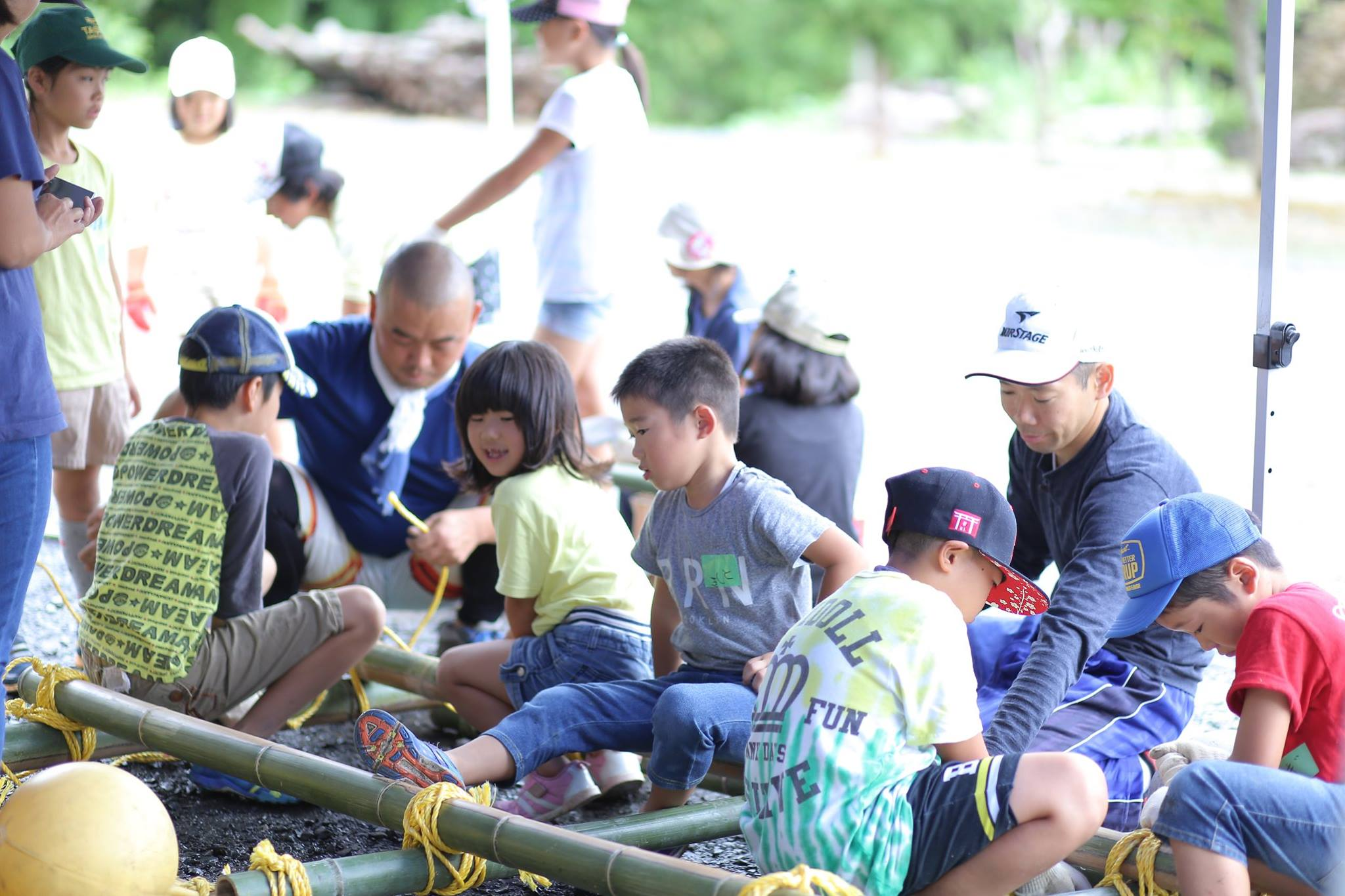two instructors teaching children how to make rafts