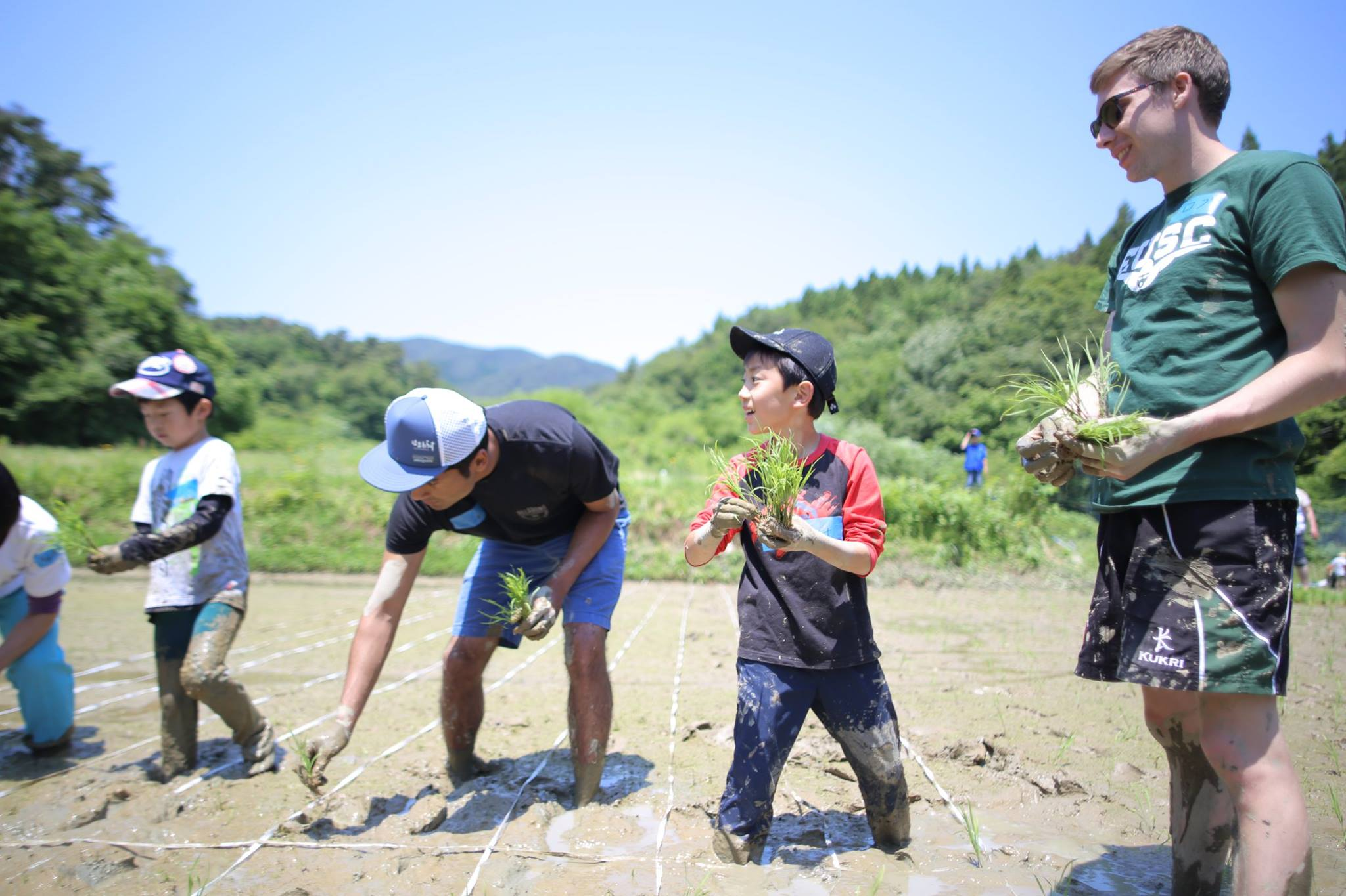 Two men and three children planting rice on a field