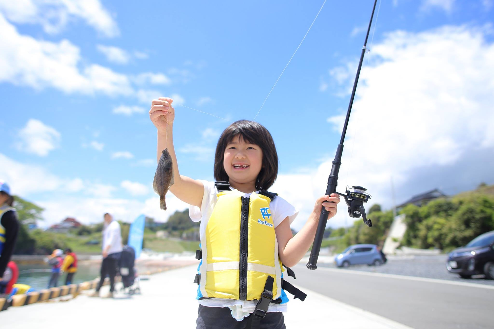 A girl holding up a fish with one hand and a fishing rod with the other