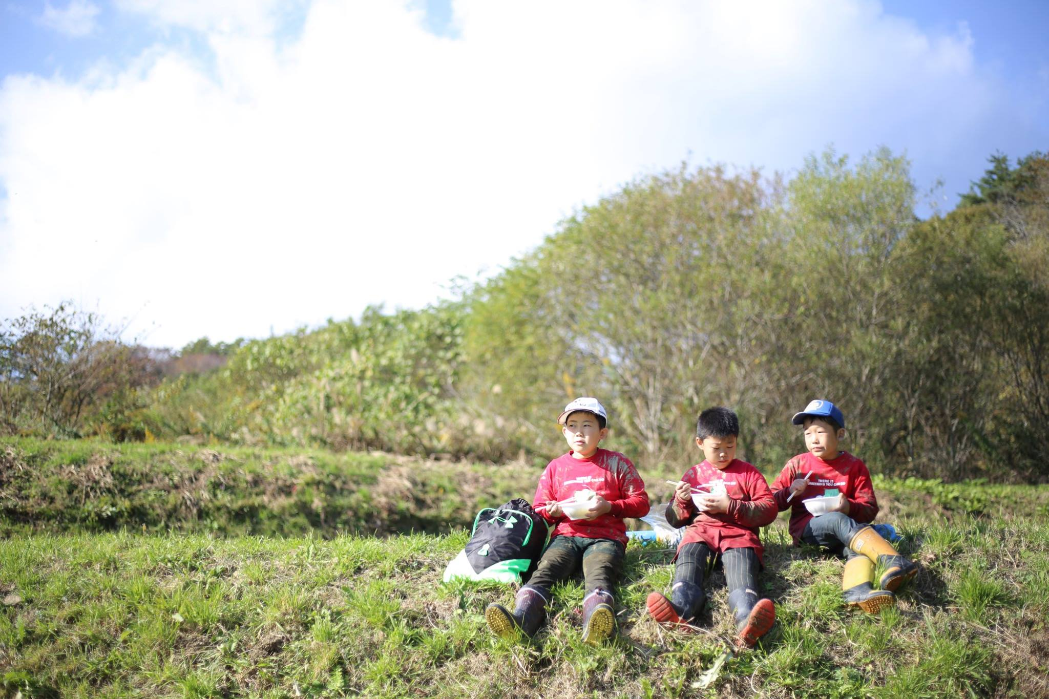 three children eating lunch while sitting on a field