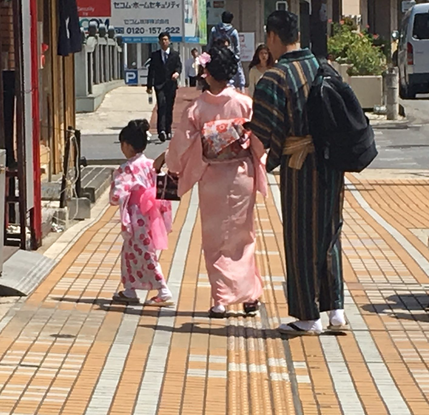 A man, a woman and a child walking down the street in traditional clothes