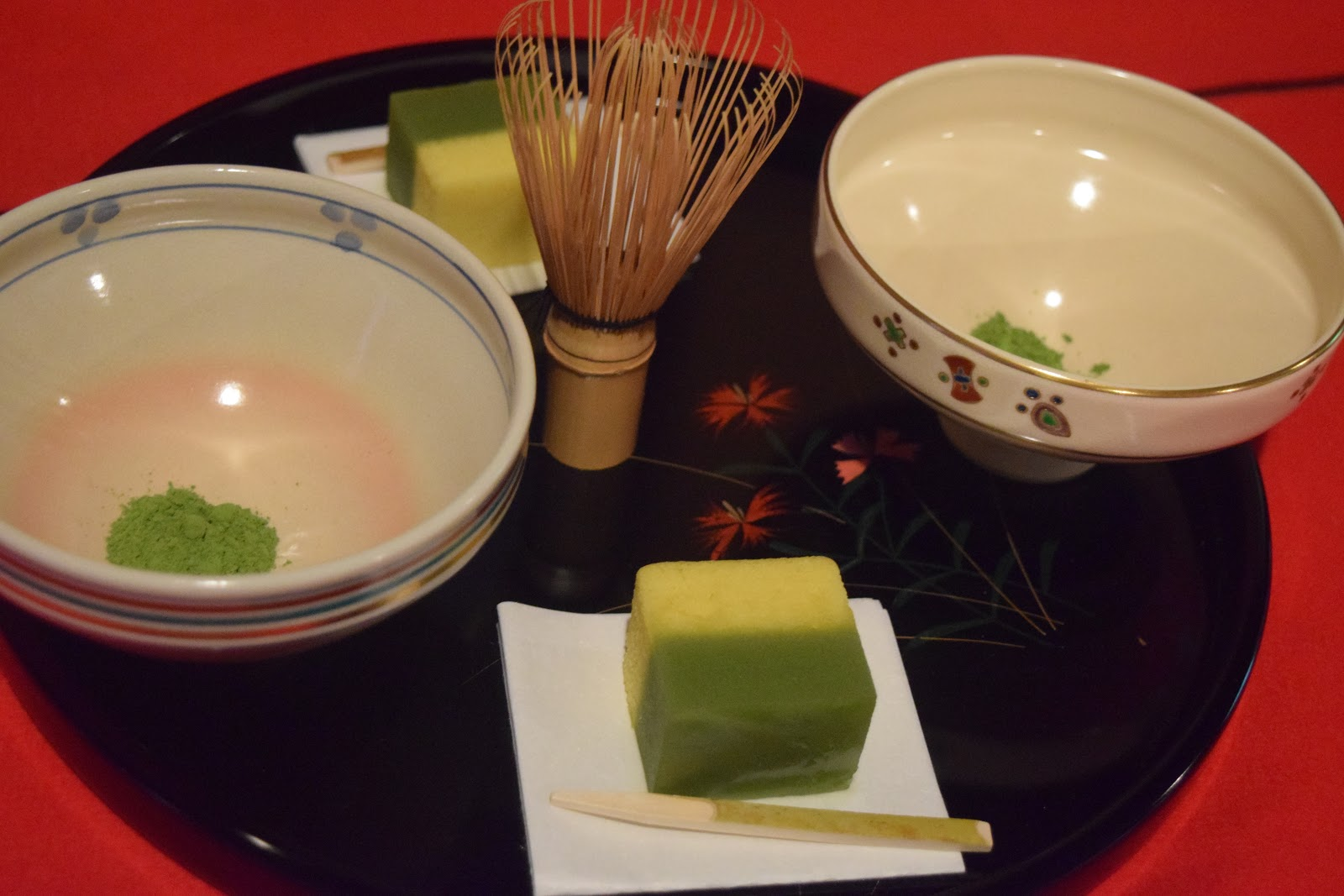 Picture displaying two tea-cups with matcha powder and two matcha cakes