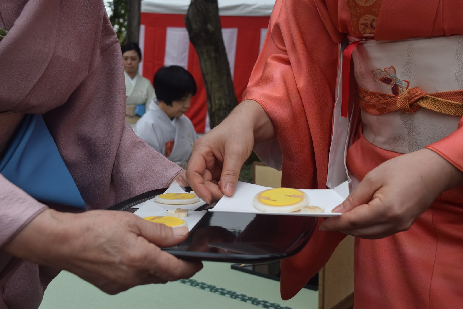 A picture of people exchanging or holding out confectionery or savory snacks