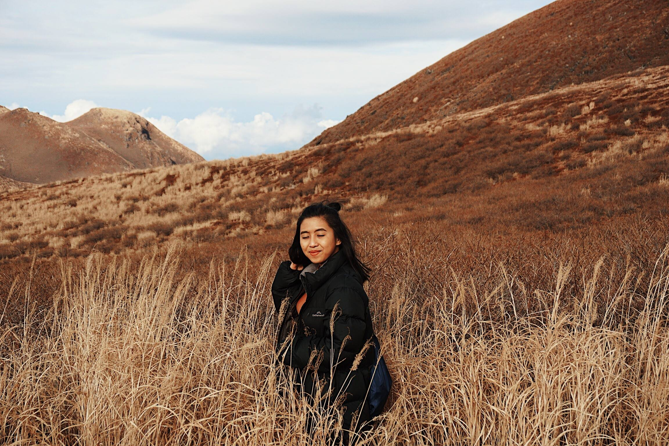 A picture of a girl amidst dried plants
