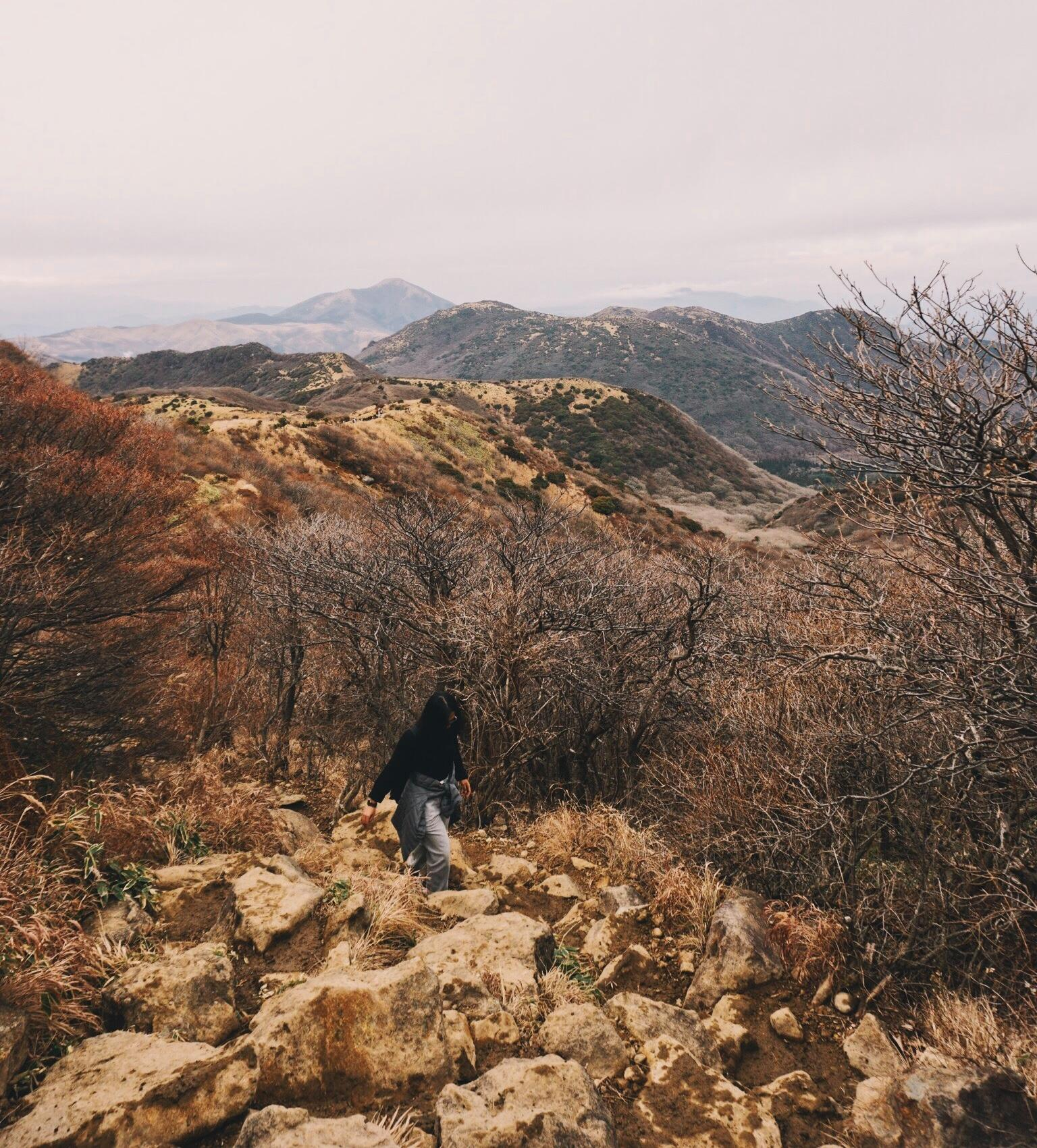 A picture of a woman sitting amidst rocks overlooking the rocky landscape