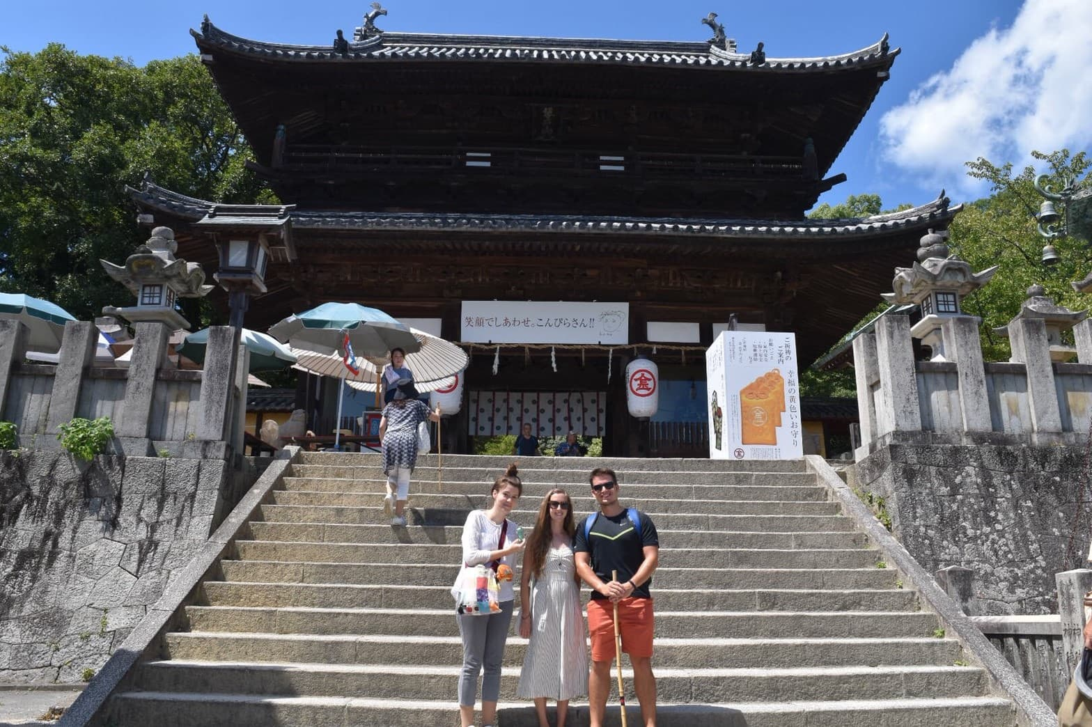 Picture of two men and a woman in front of the Shrine
