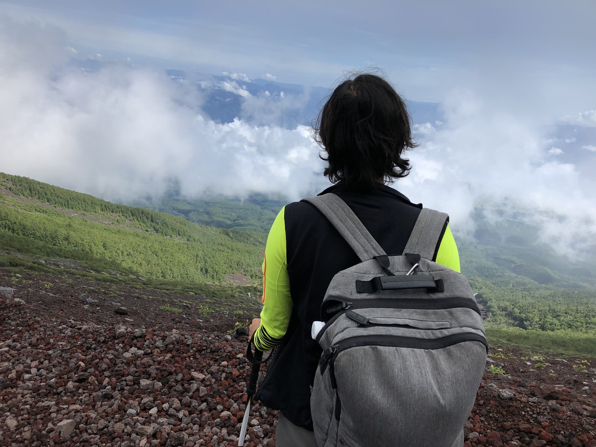 A picture of a woman with a backpack standing with her back to the camera looking at a view of the mountain cradled with clouds