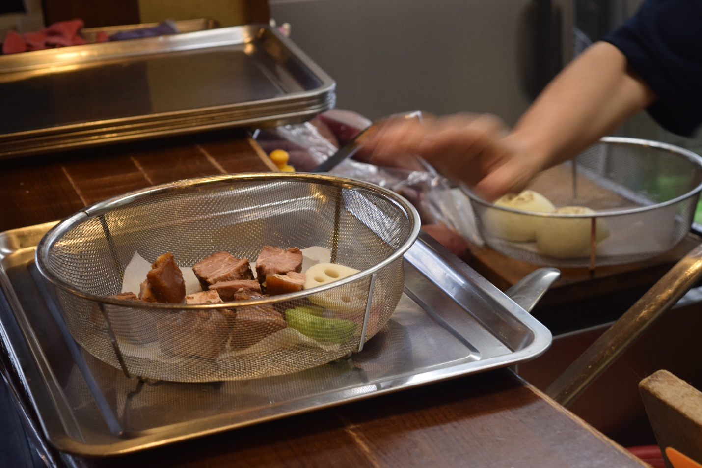 Picture of a steel colander with an assortment of meat slices and vegetables being readied for steaming