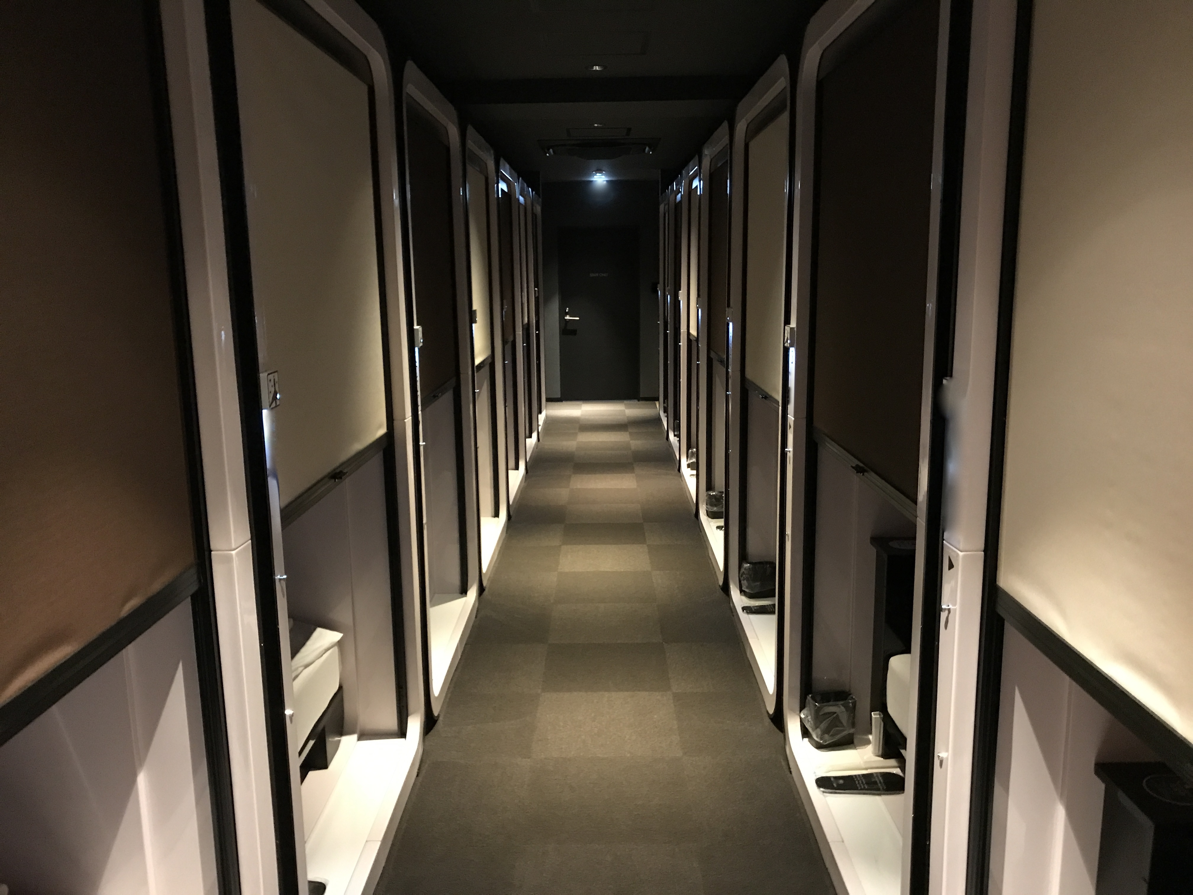 A picture of a corridor with capsule hotel rooms