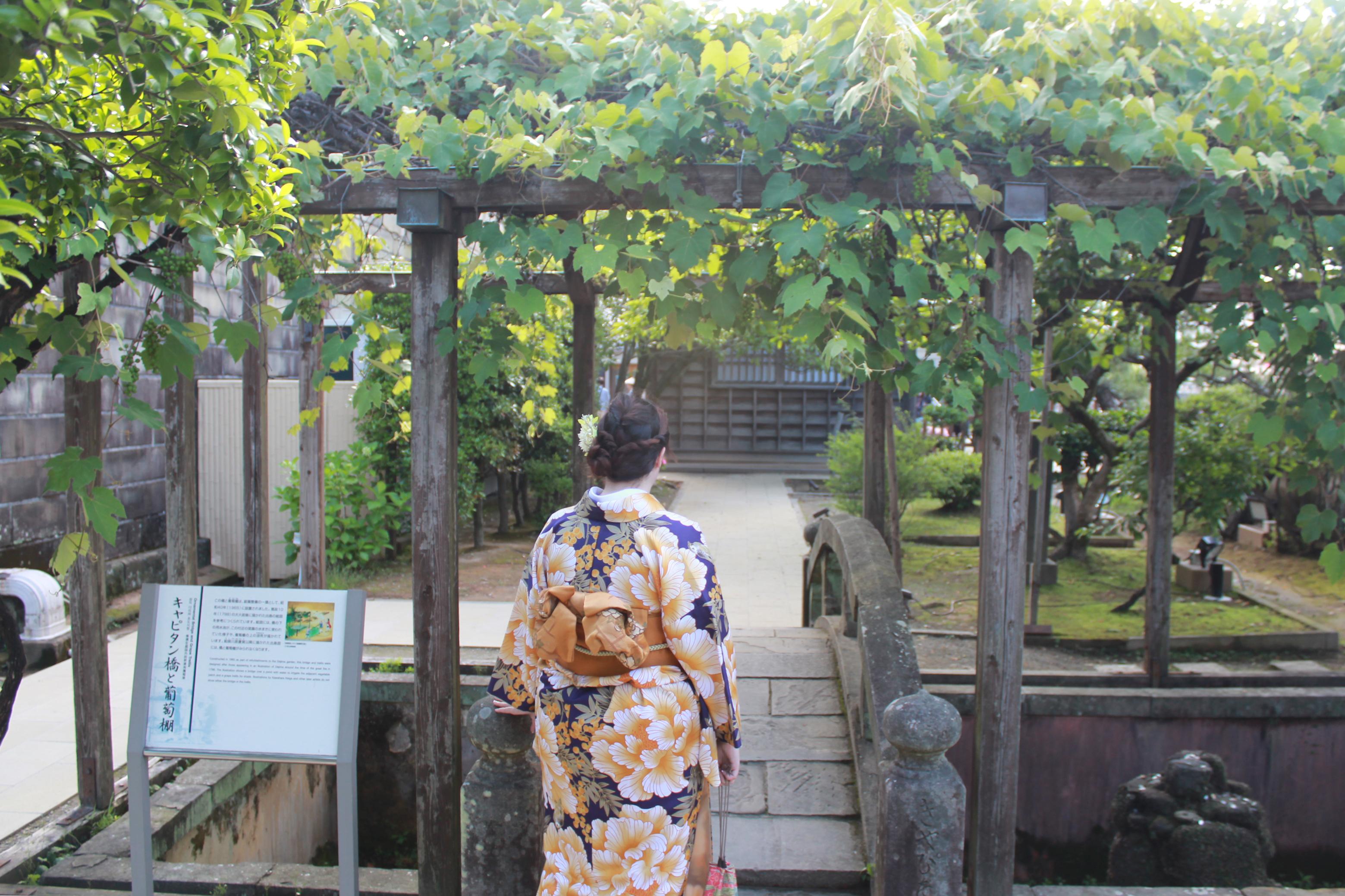 A person in kimono walking on a stone bridge in a garden