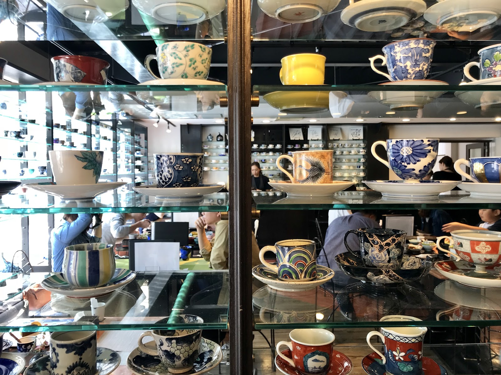 A picture of a shelf displaying the varied cup and saucer combinations