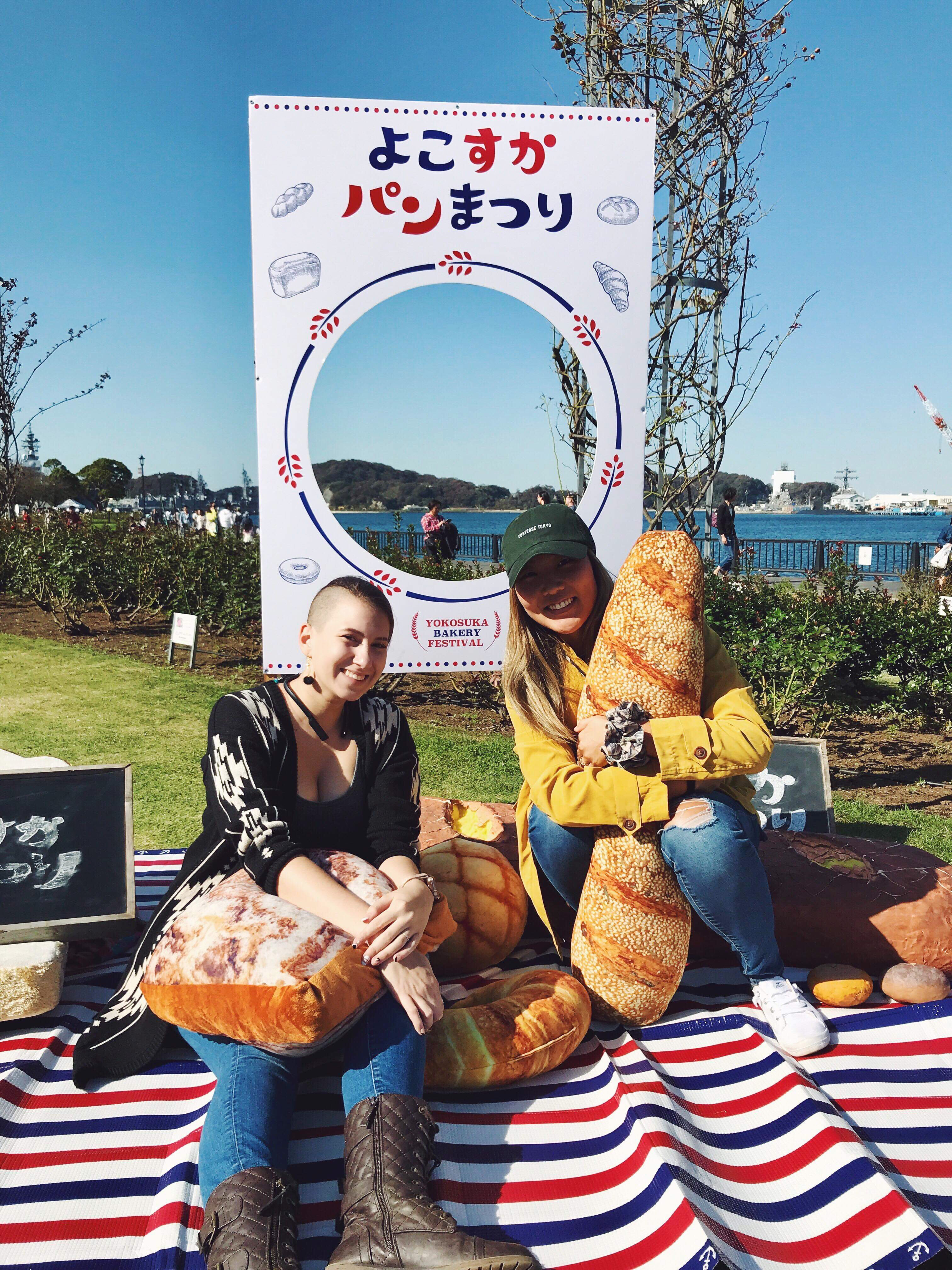 A picture of two women sitting upon a picnic blanket on the grass at the festival grounds