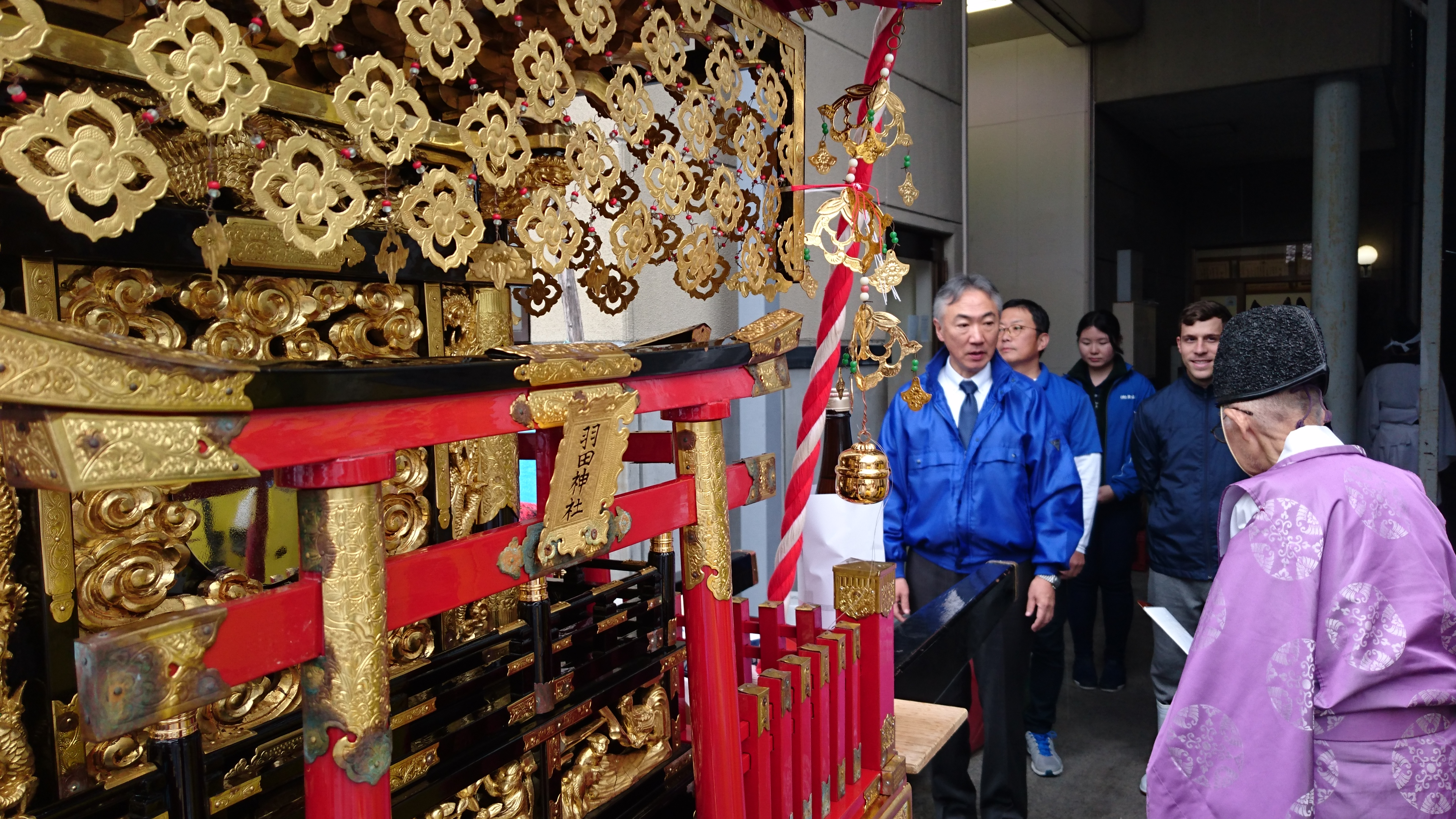 Picture of the head priest standing in front of the shrine, with other people standing by a sake brewery