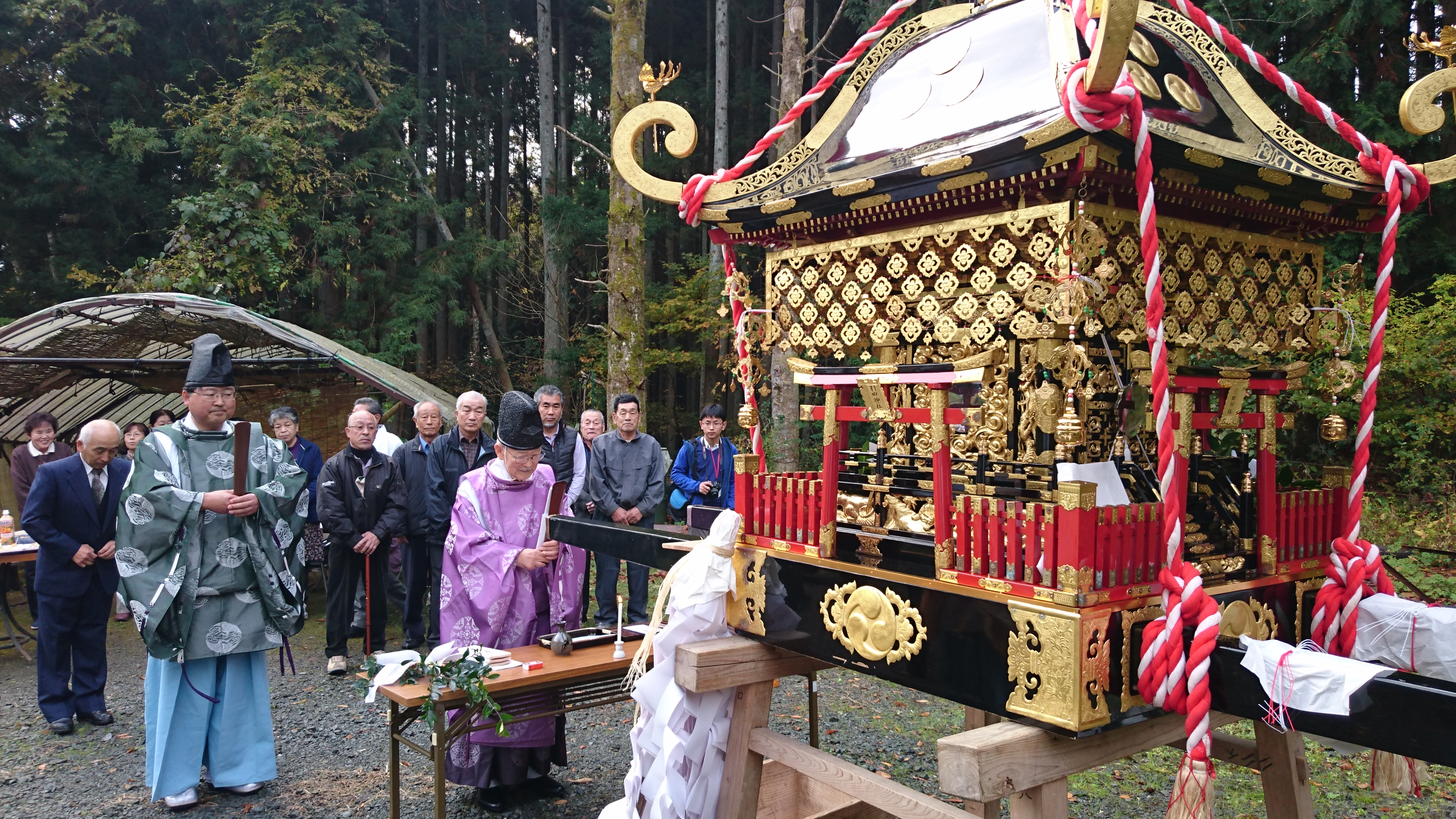 Picture of the head priest offering prayers to the portable shrine