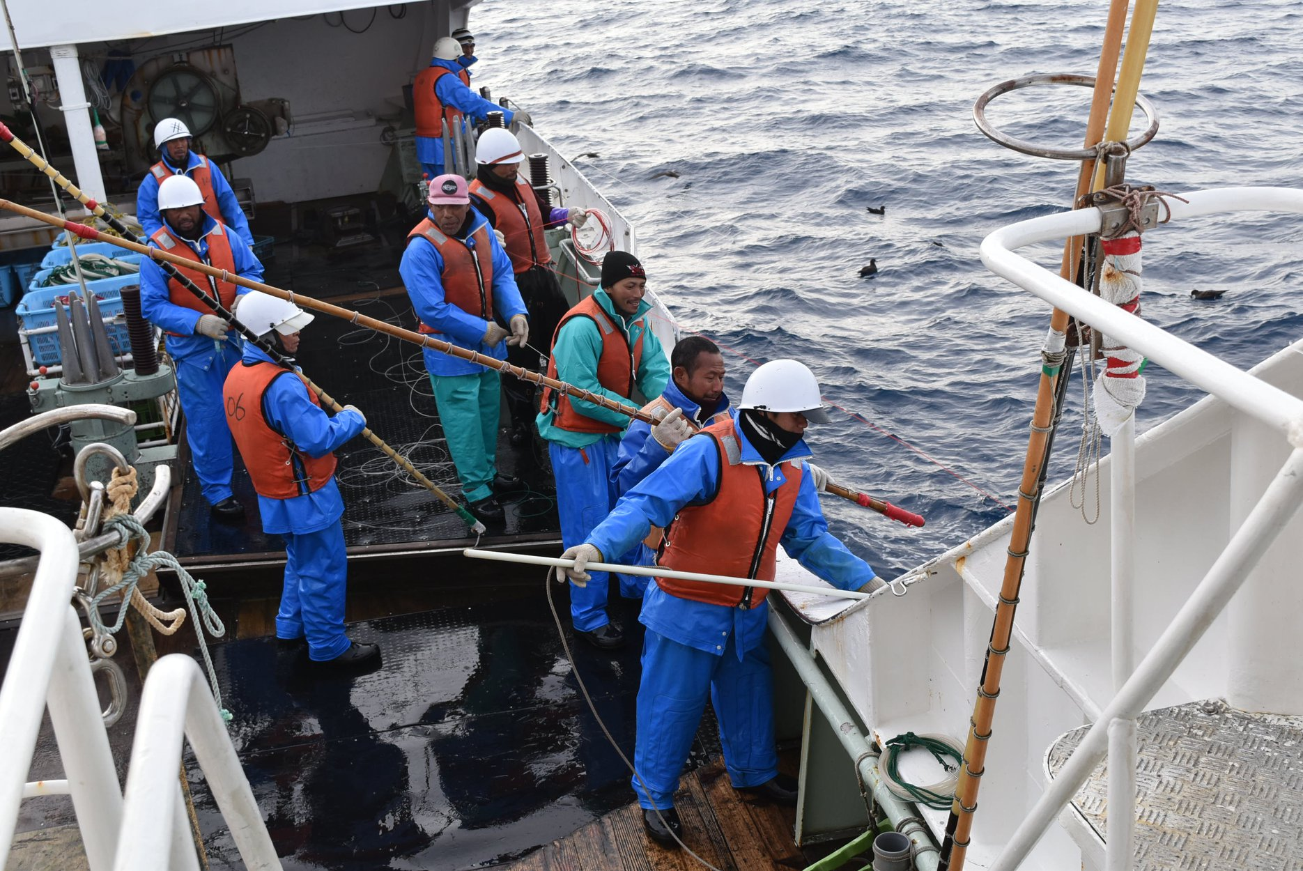 Picture of nine fishermen on a ship dressed in red and blue uniforms holding a rope