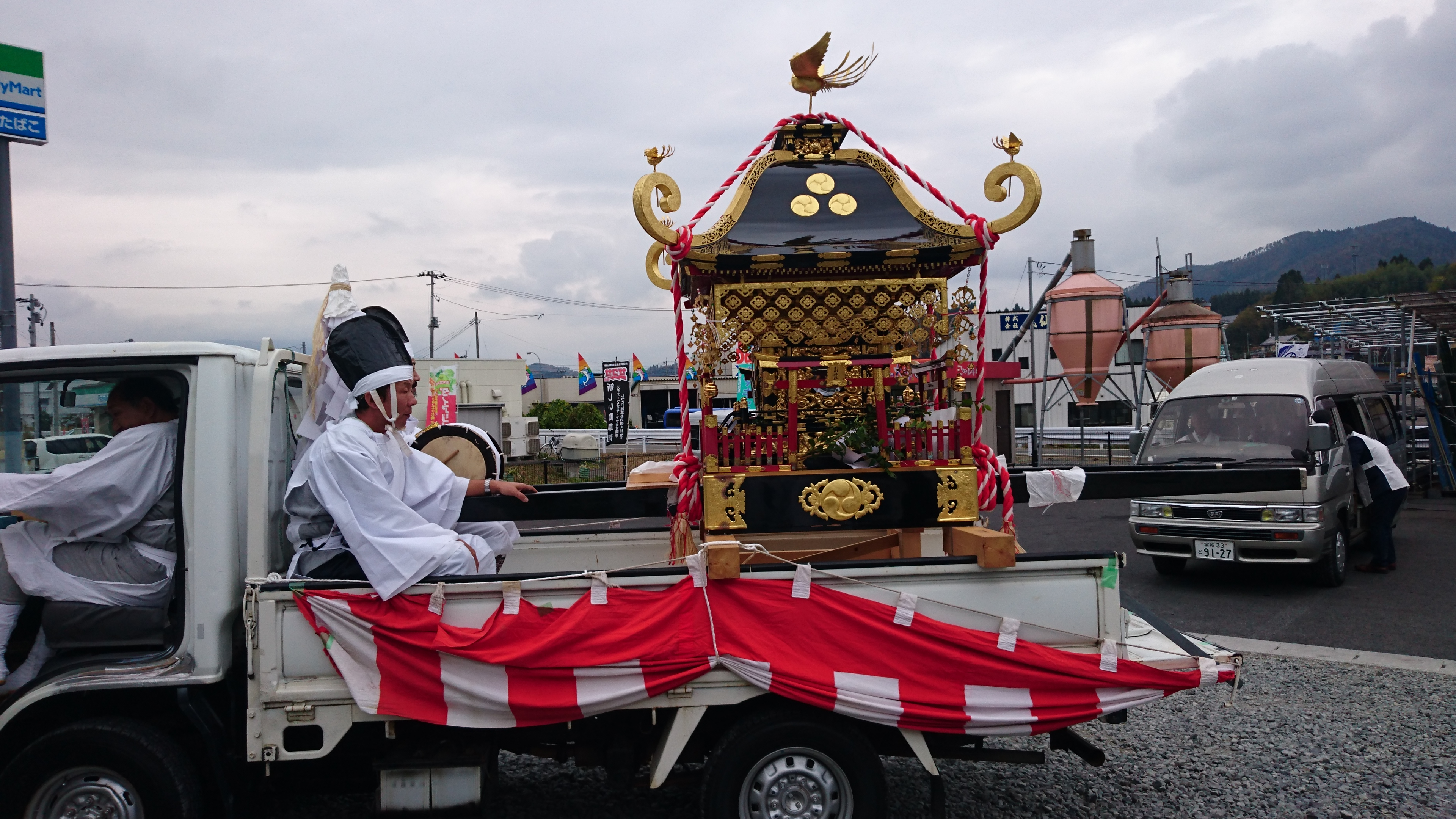 Picture of two young men in white robes traveling with the portable shrine on the back of a truck