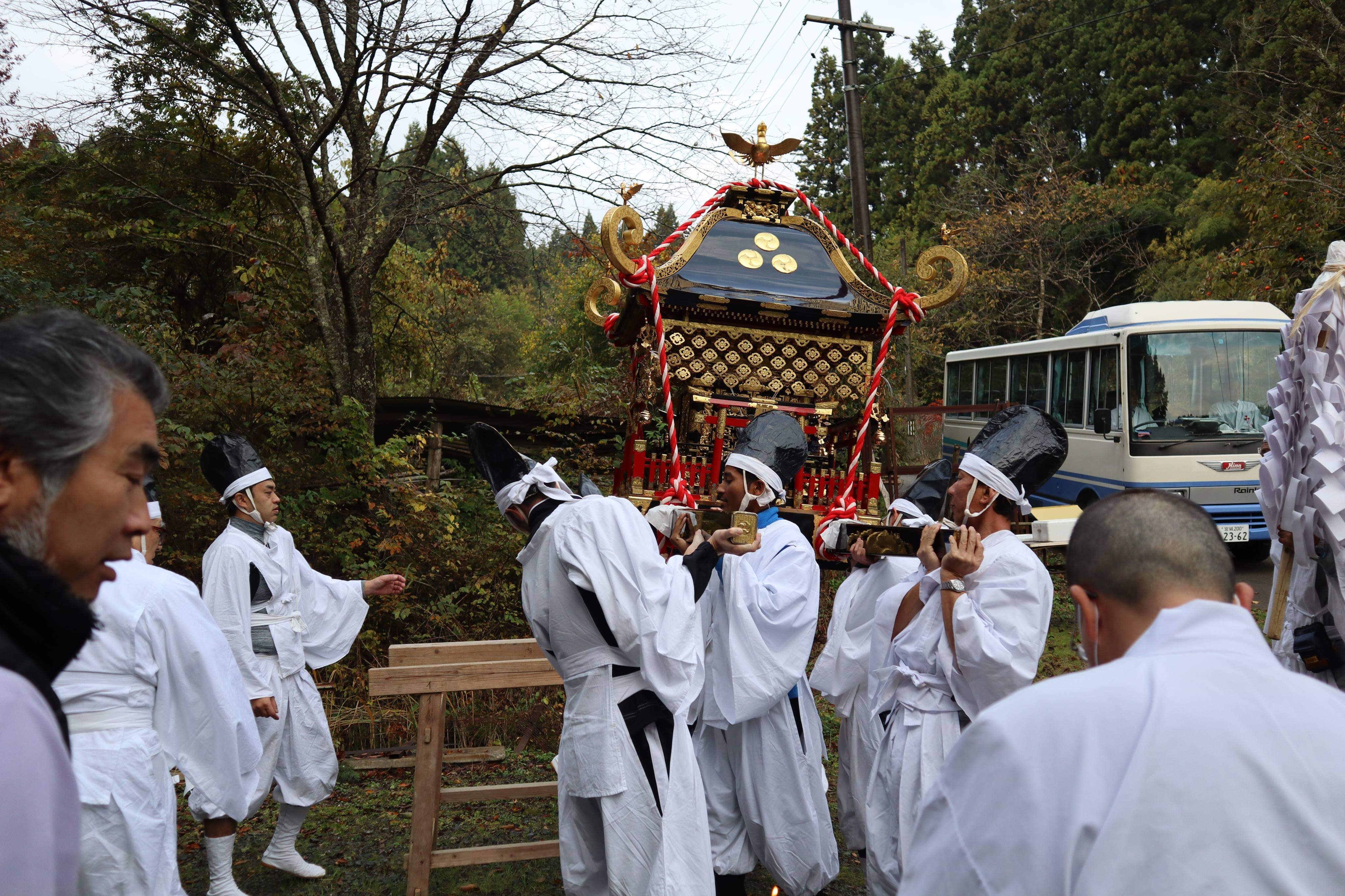 Picture of the young men in white robes attempting to pick up the portable shrine