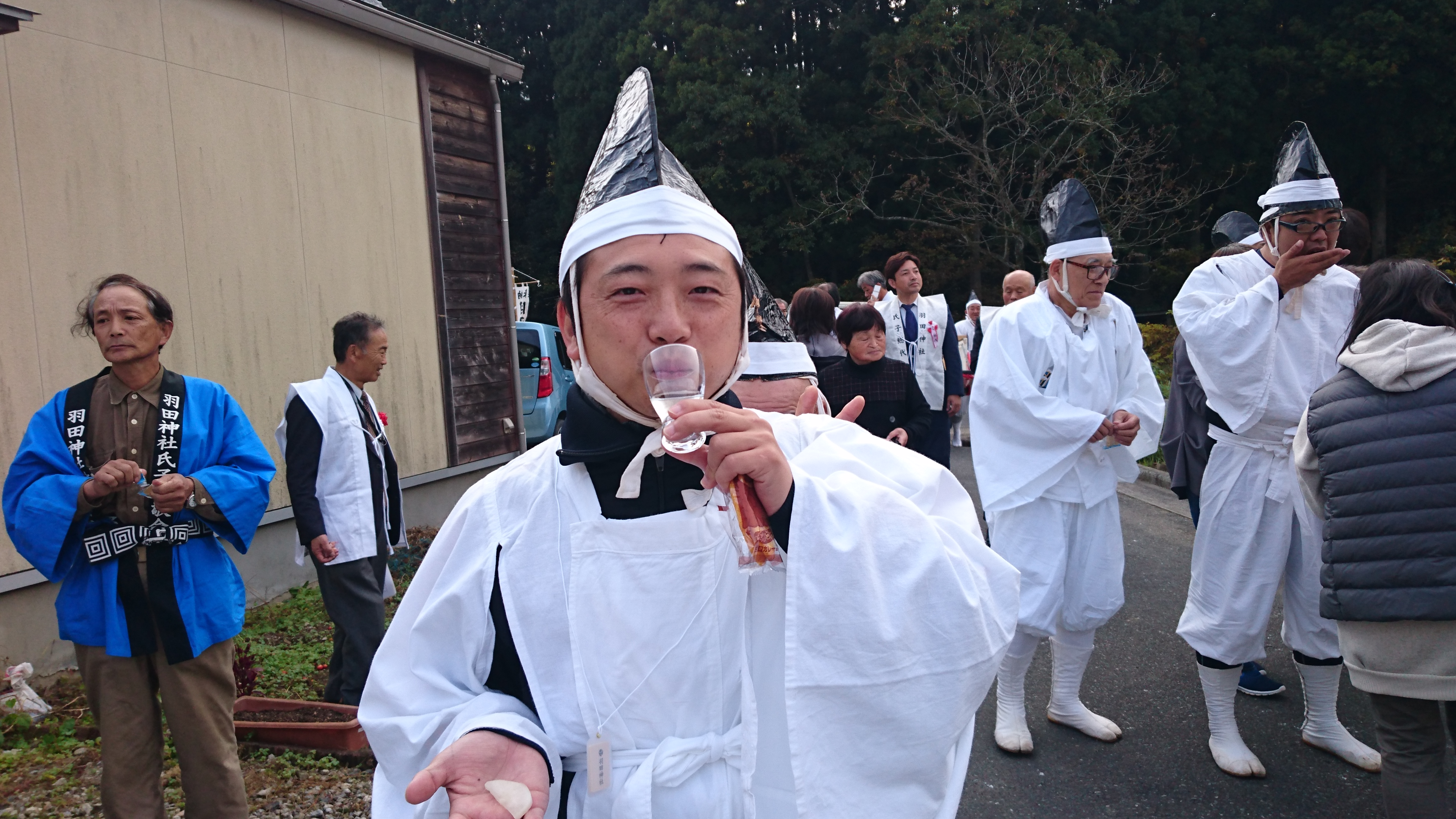 Picture of a man in a white robe drinking sake