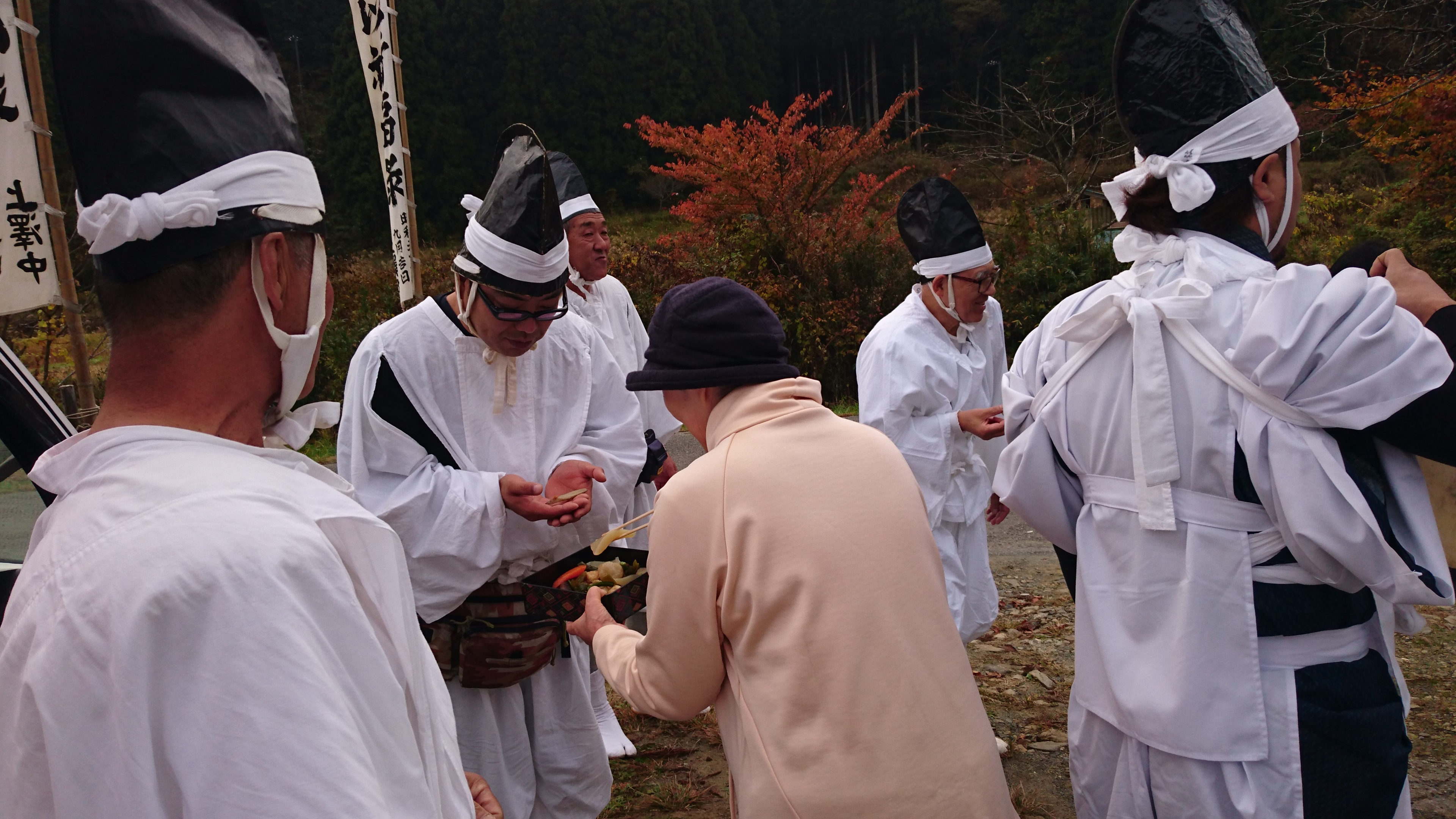 Picture of a few men gathering around a stall offering light refreshments