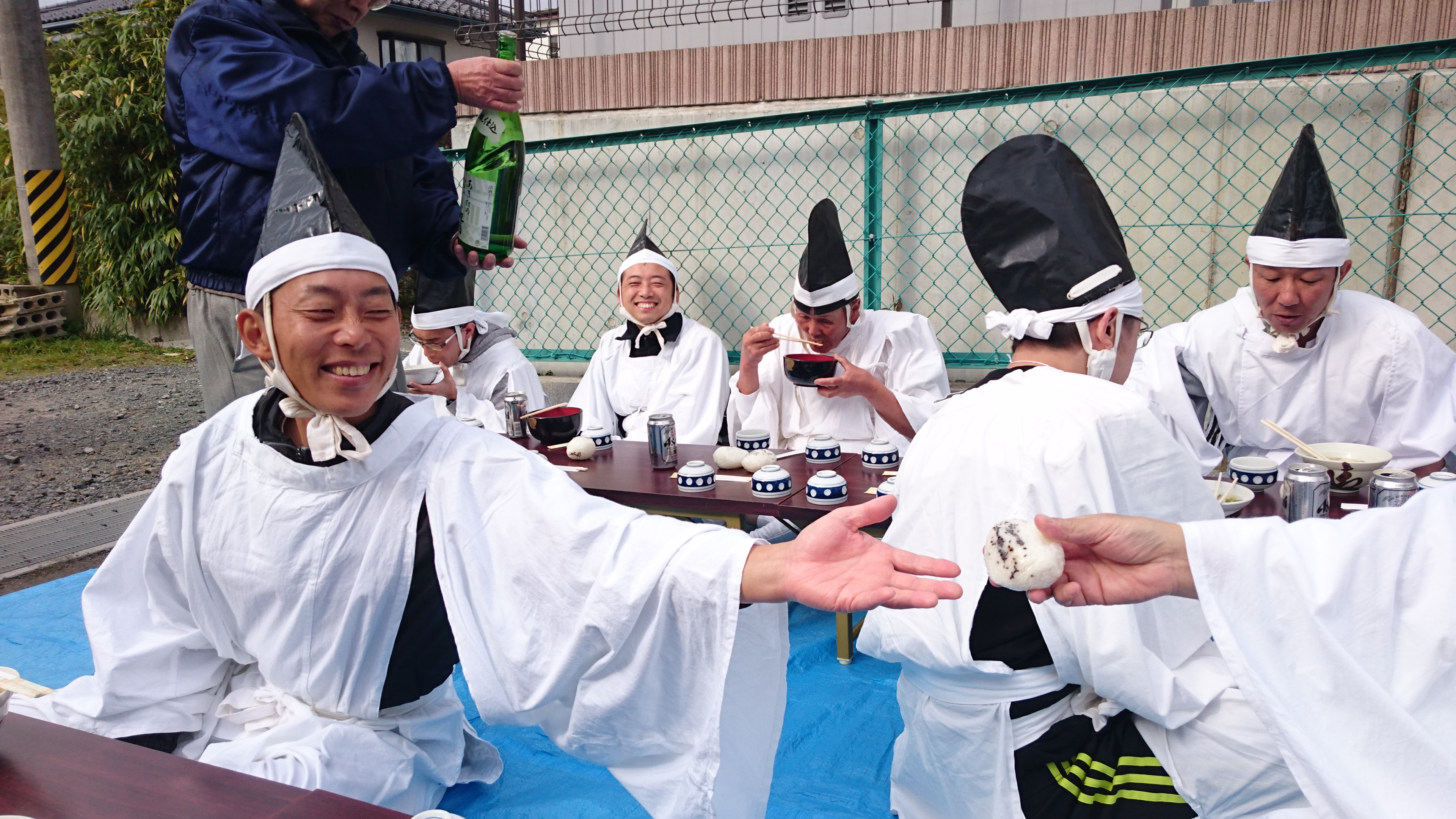 Picture of a man holding out an onigiri to another man, with the backdrop of other men enjoying soup