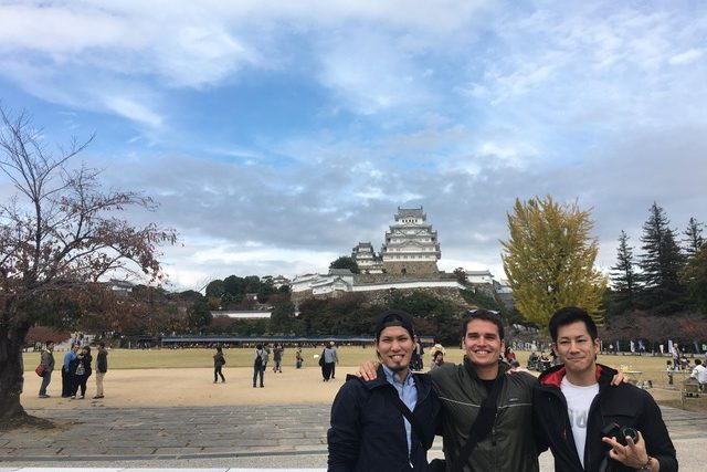 A picture of three men with the castle in the backdrop and large space with benches in front of the castle