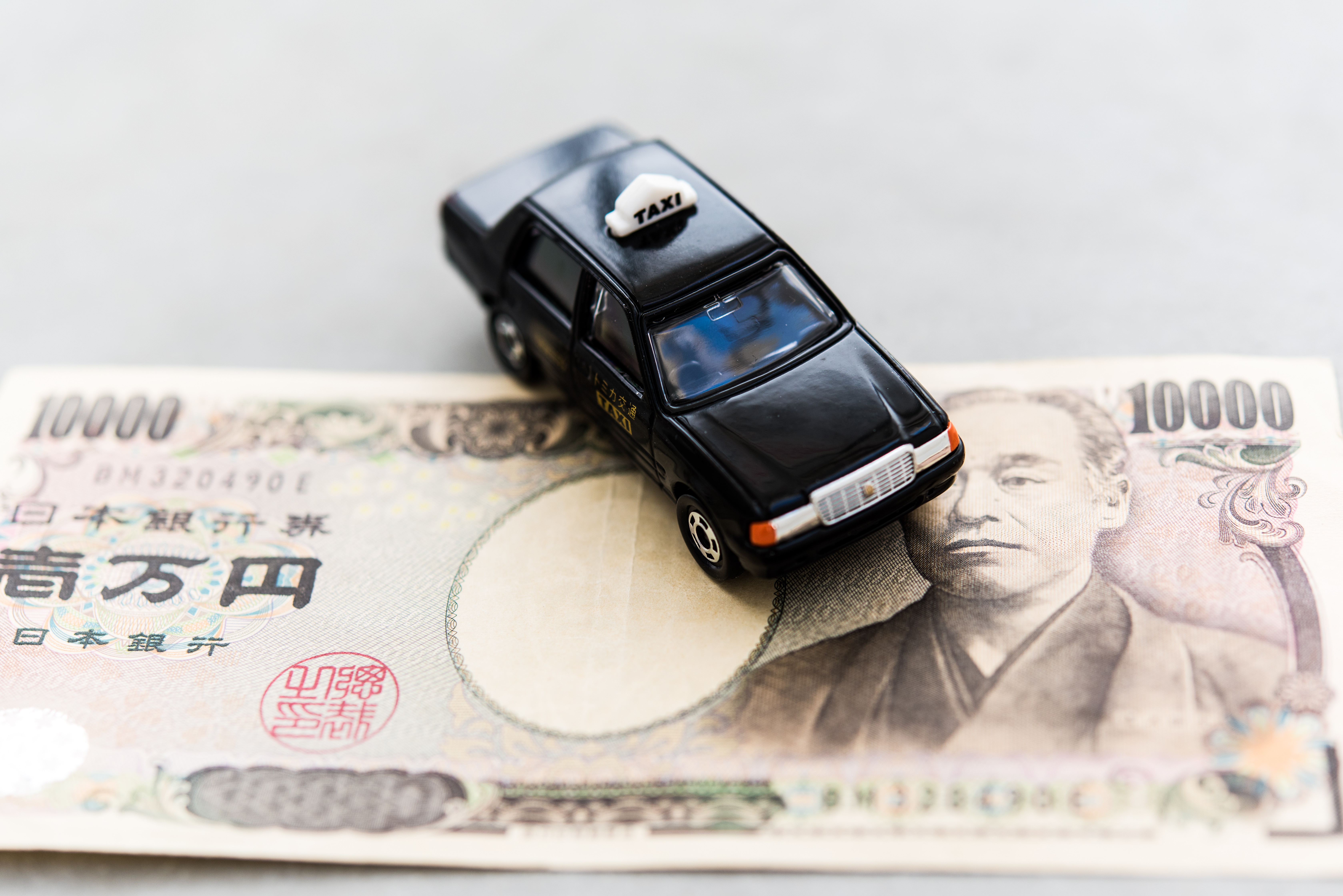 A picture of a toy taxi on top of a Japanese yen note