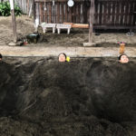 three people buried in a sand bath