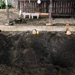 three people buried in a sand bath