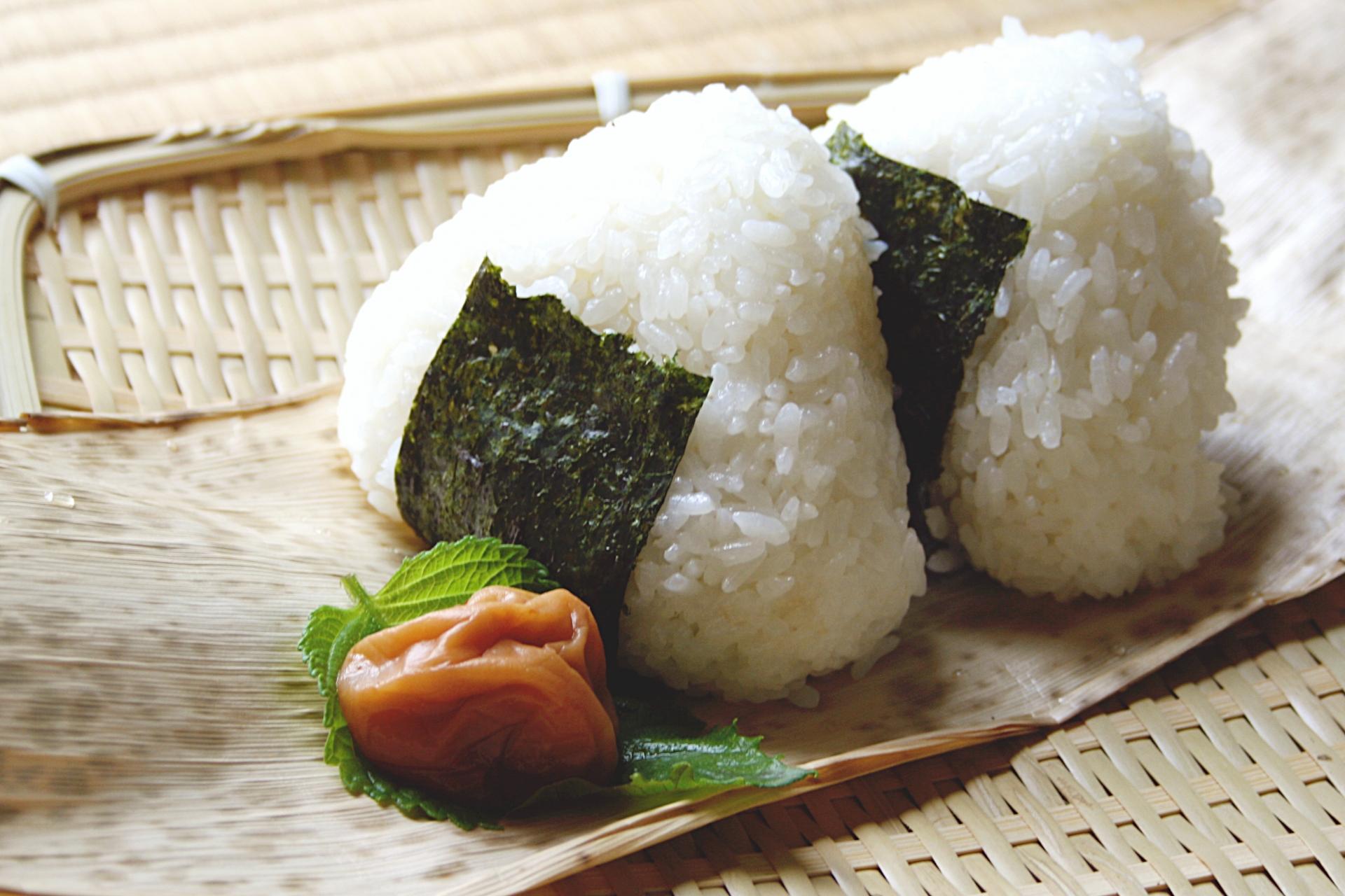 Two onigiri rice balls and umeboshi on a bamboo leaf