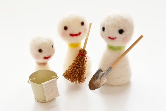three snowman dolls with a broom, a shovel and a bucket
