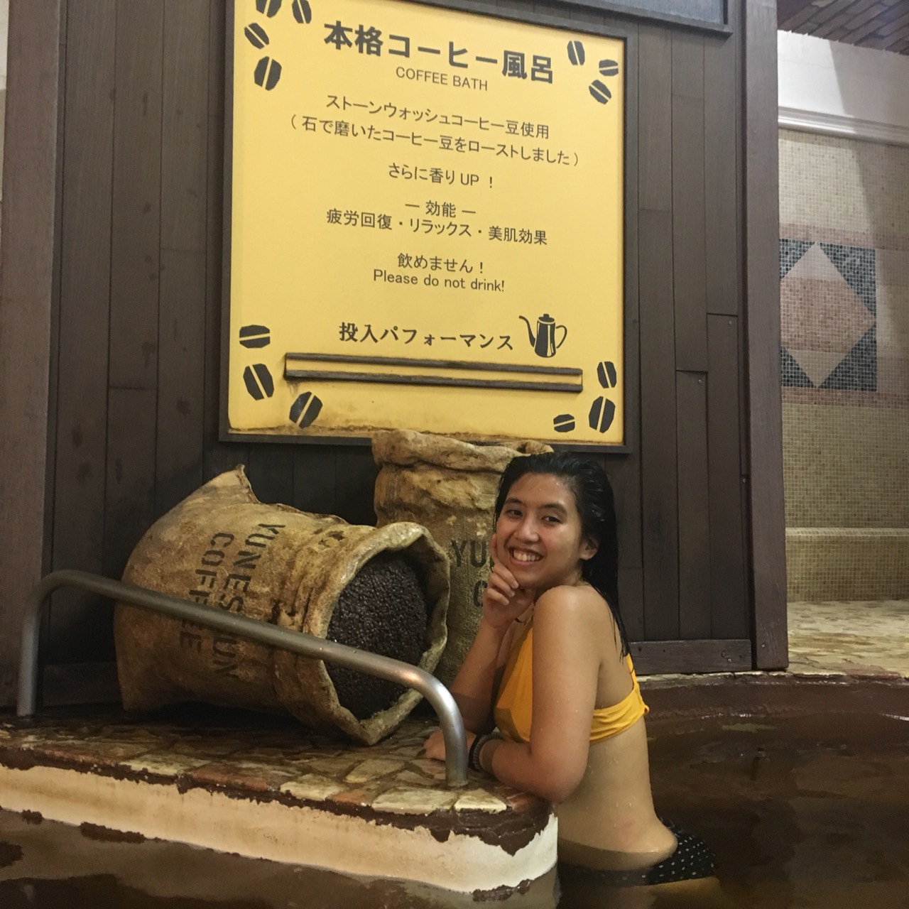 "A person posing in a bathtub with coffee bean sacs and a sign that says ""Coffee Bath"" in the background"