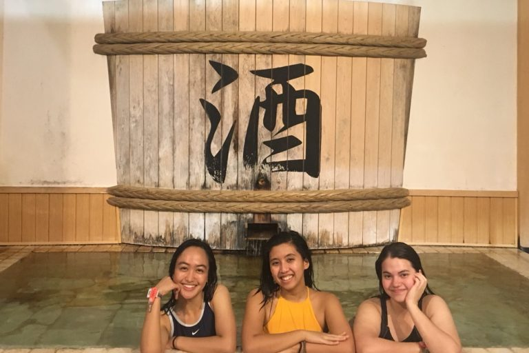 Three people posing in an onsen with a big sake barrel in the background
