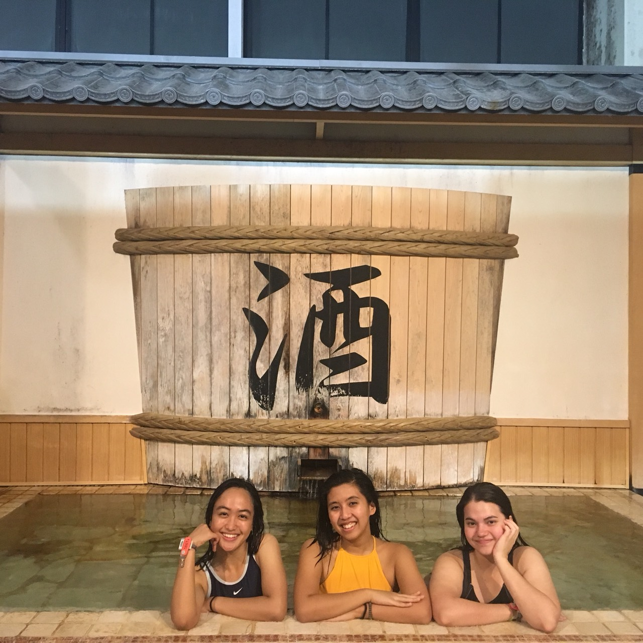 Three people posing in a bathtub with a large sake barrel in the background