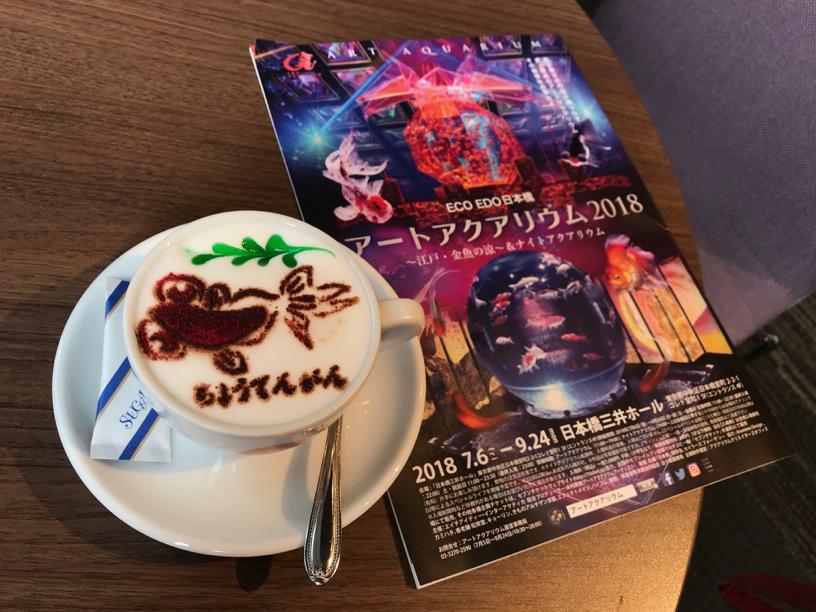 a goldfish-themed latte art and a leaflet of Art Aquarium 2018