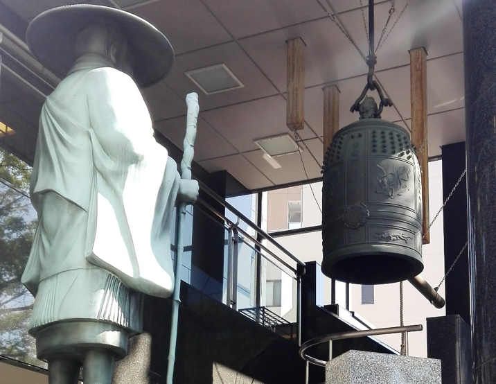 a Buddhist temple bell and a statue of a monk