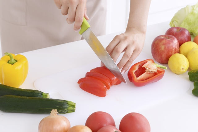 a close-up photo of a person cutting vegetables