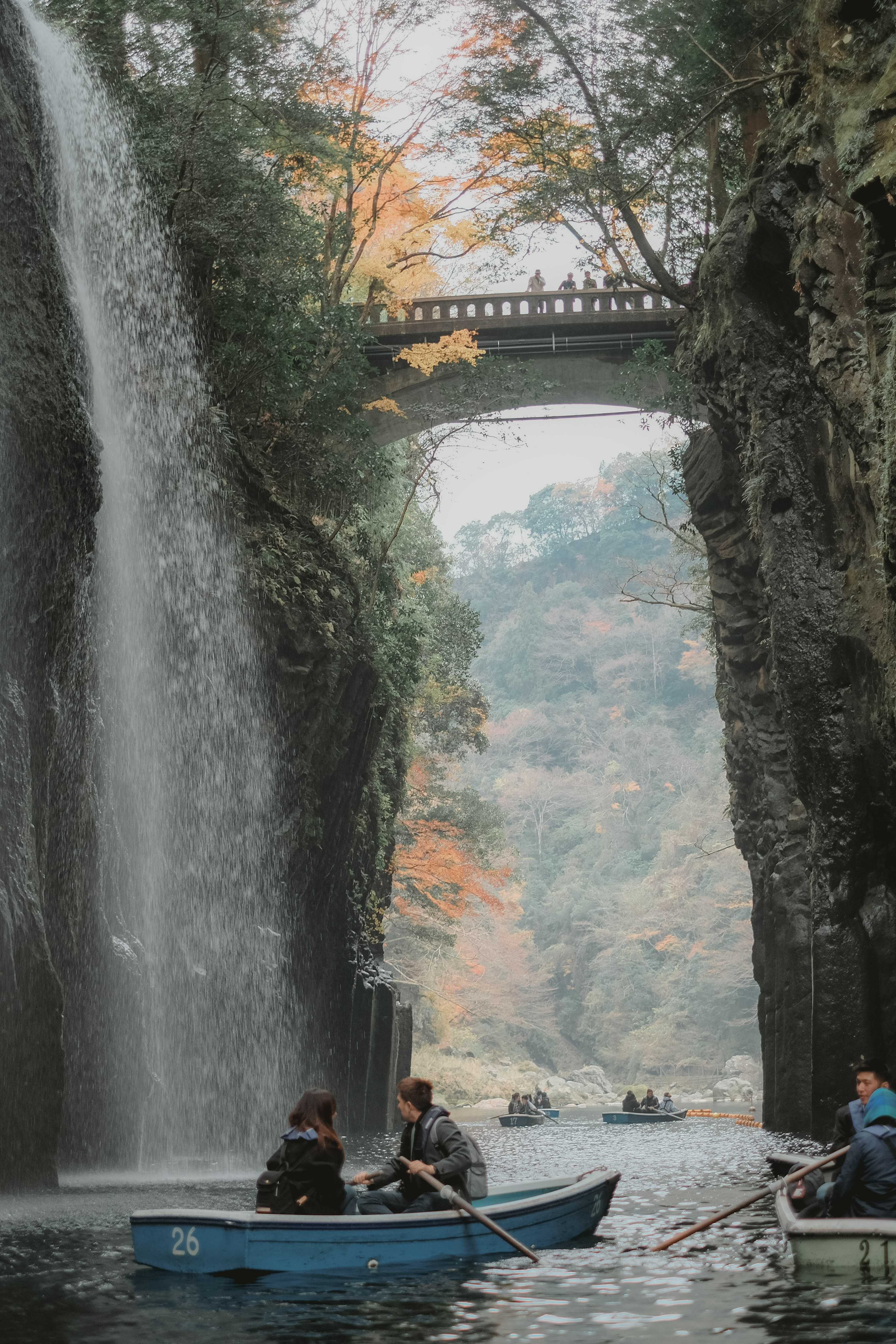 two people paddling a boat with a waterfall and a bridge in the background