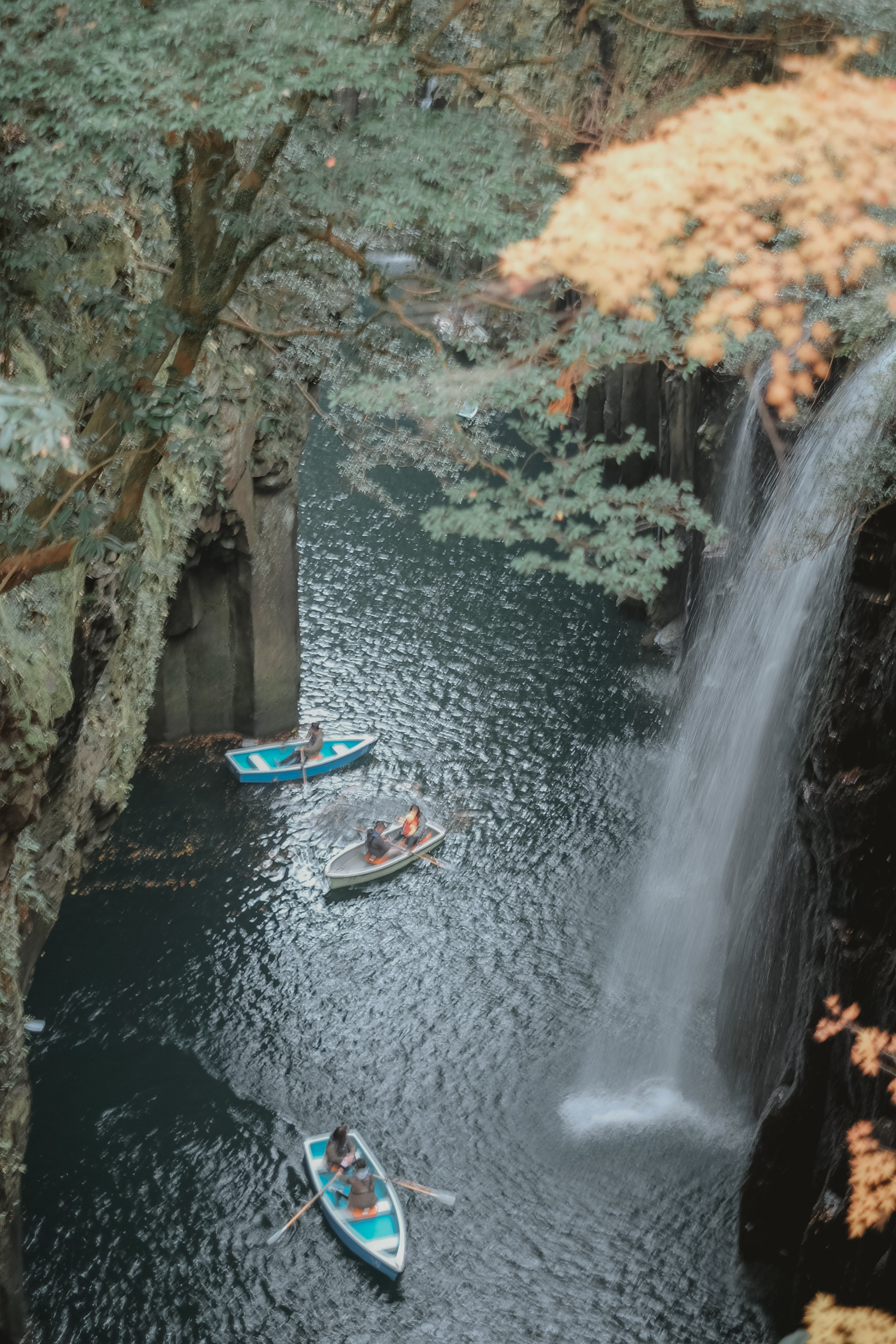three paddle boats floating on a river with a waterfall on their side