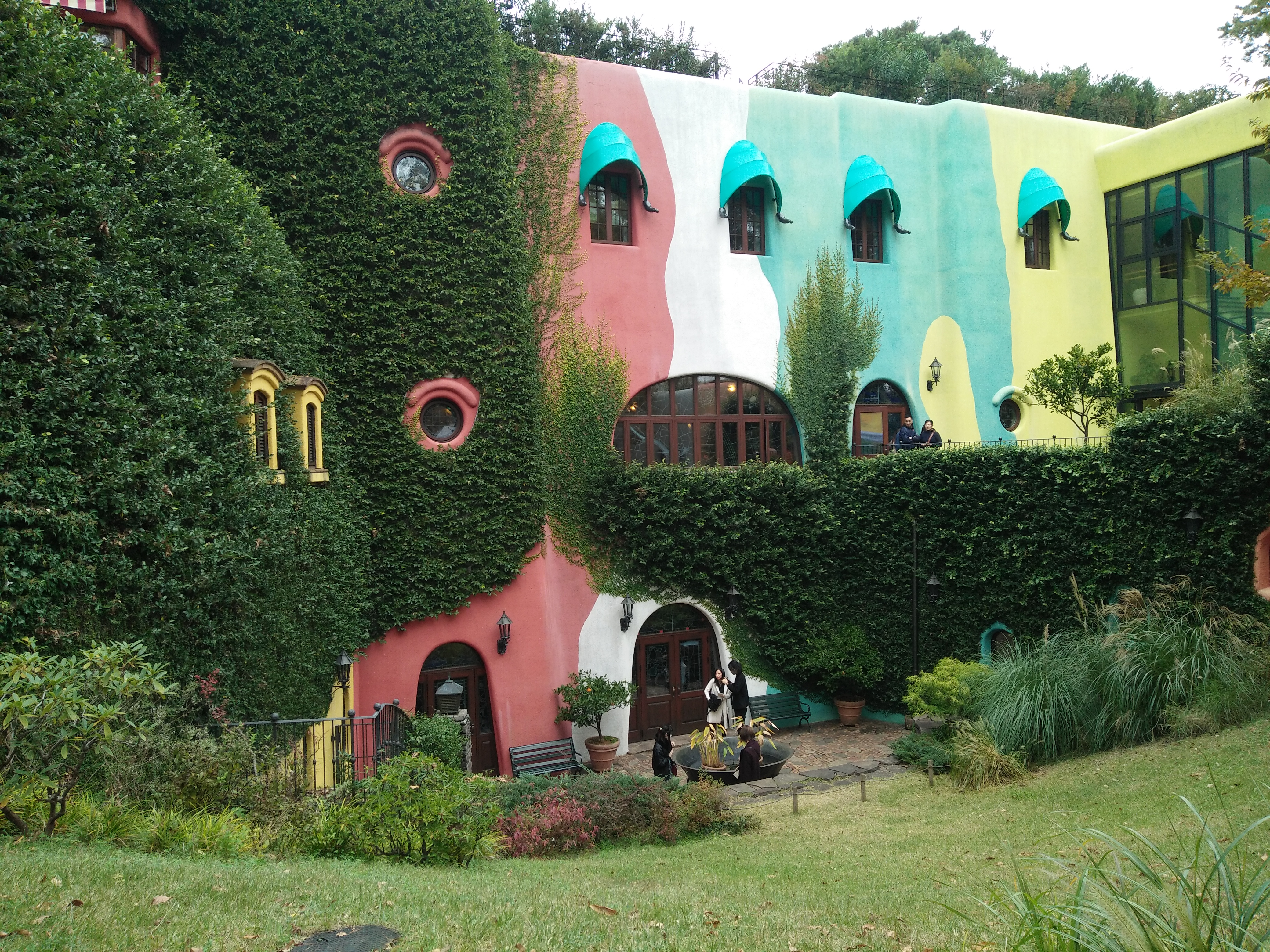 Picture of the quirky museum building painted in bright pink, white, green and