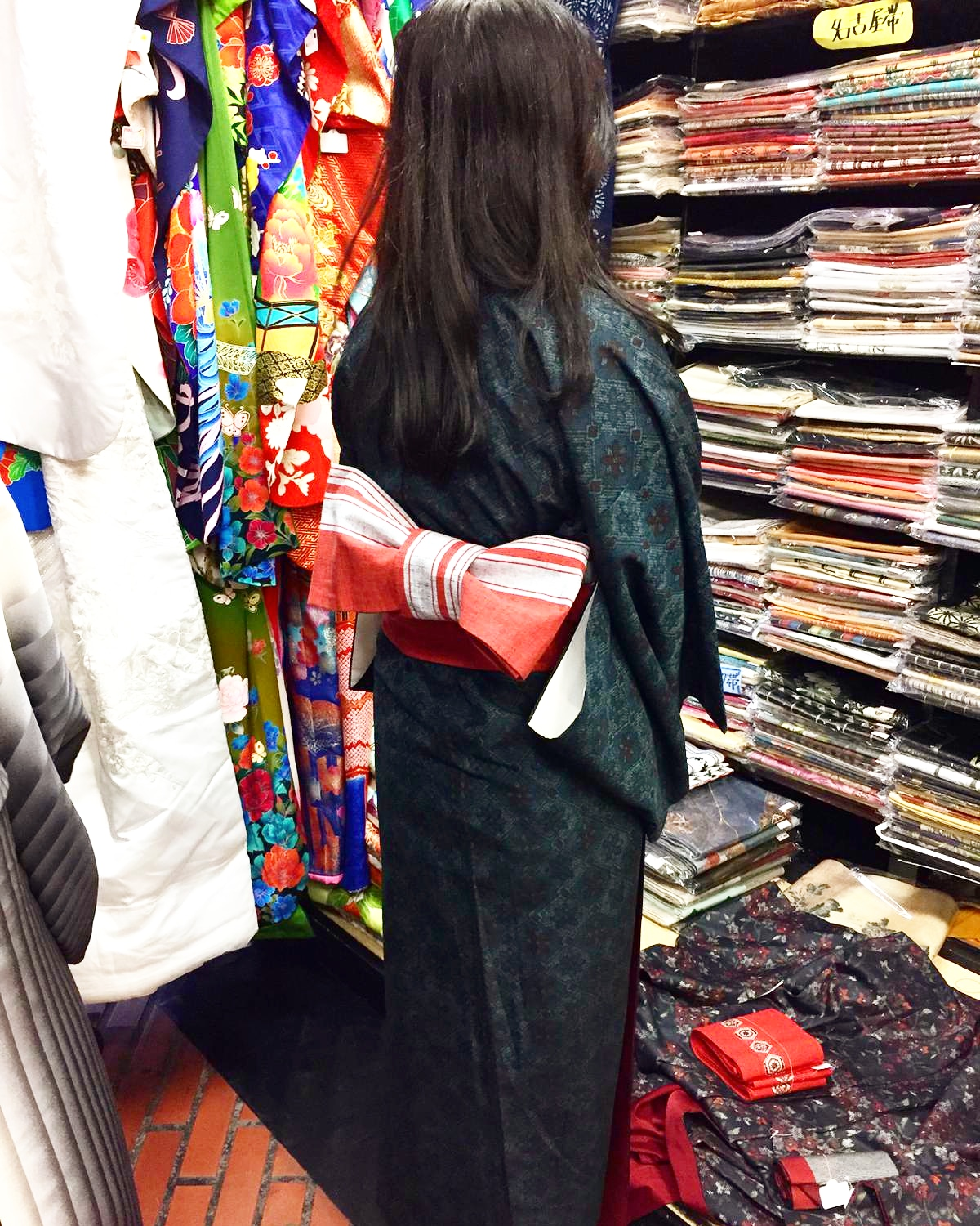 Picture of a woman trying on a kimono inside the shop