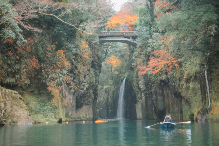 a gorge with a waterfall and a bridge in the background